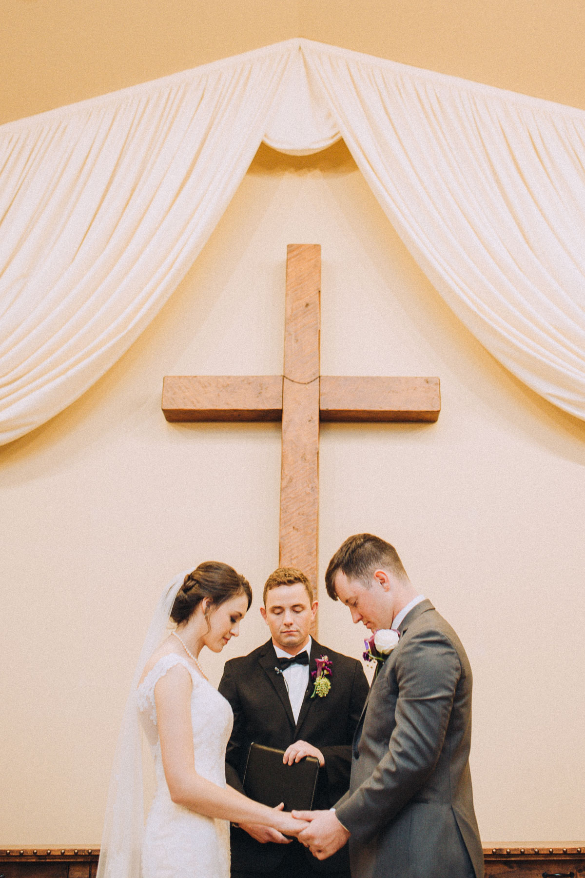 Bride and groom bowed in prayer during their wedding ceremony at Wedgewood Black Forest.