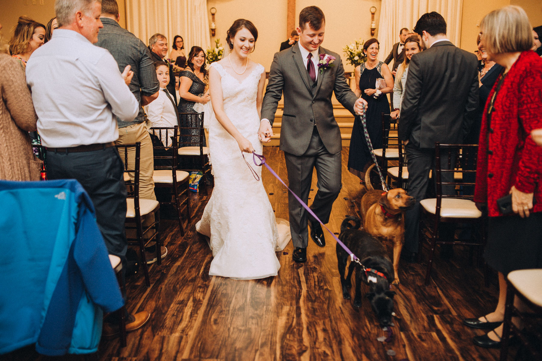 Bride and groom exit wedding ceremony with dogs on leash.