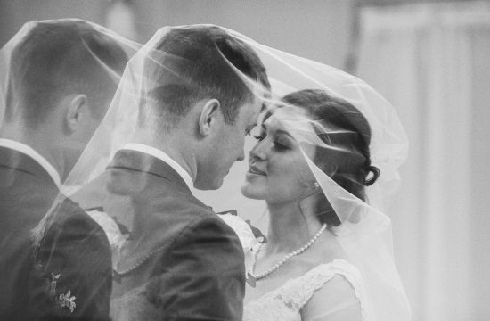 Black and white photo of bride sharing a kiss underneath her wedding veil with groom.