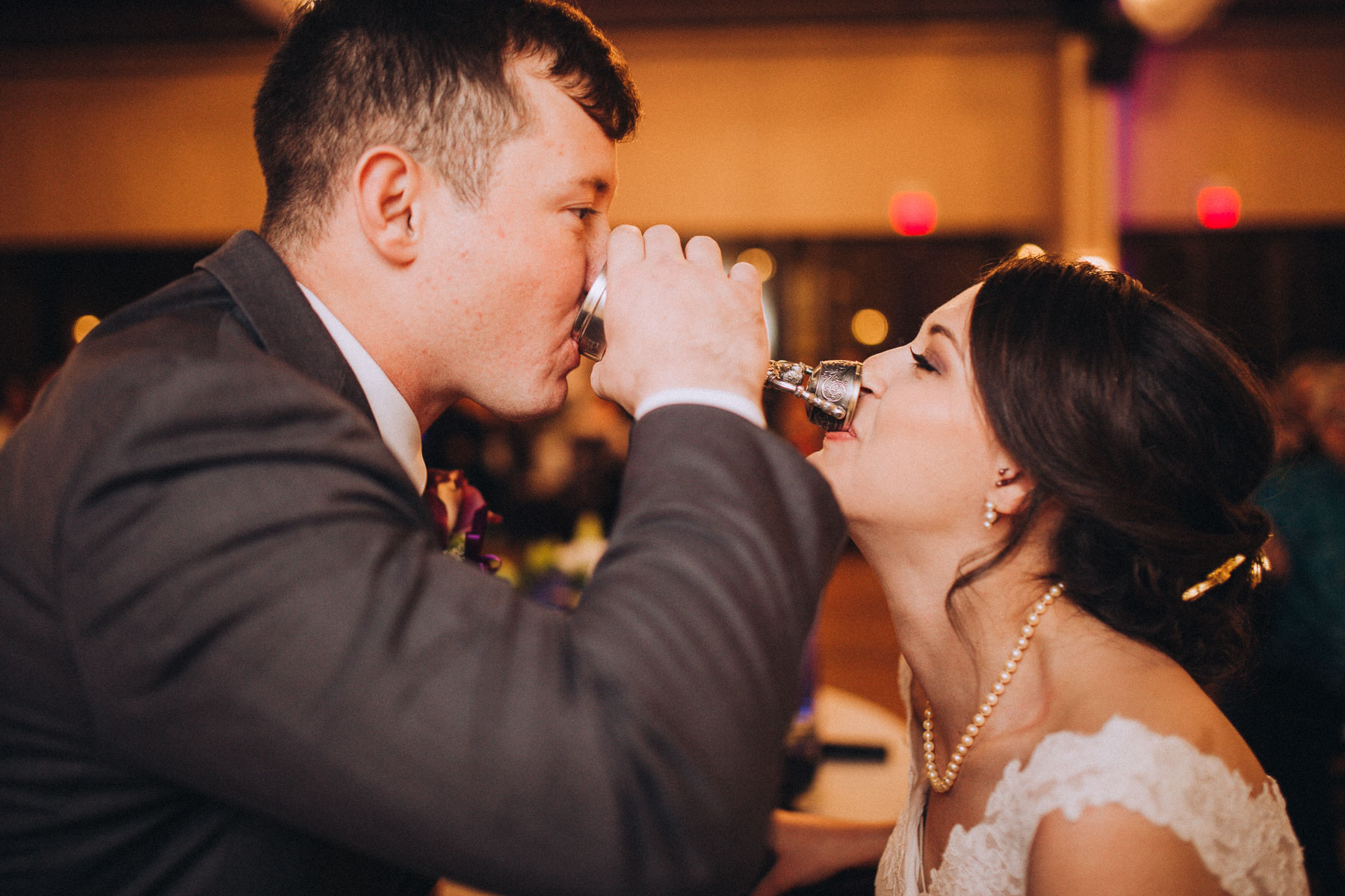 Bride and groom share a drink in a two-cup toast during their wedding reception at the Wedgewood Black Forest.