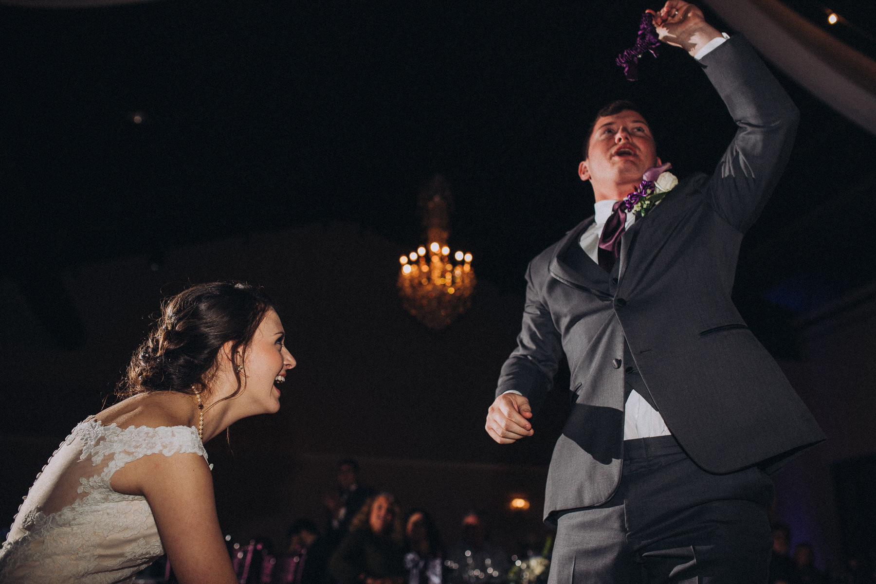 Bride laughs as groom removes garter during wedding reception at Wedgewood Black Forest.