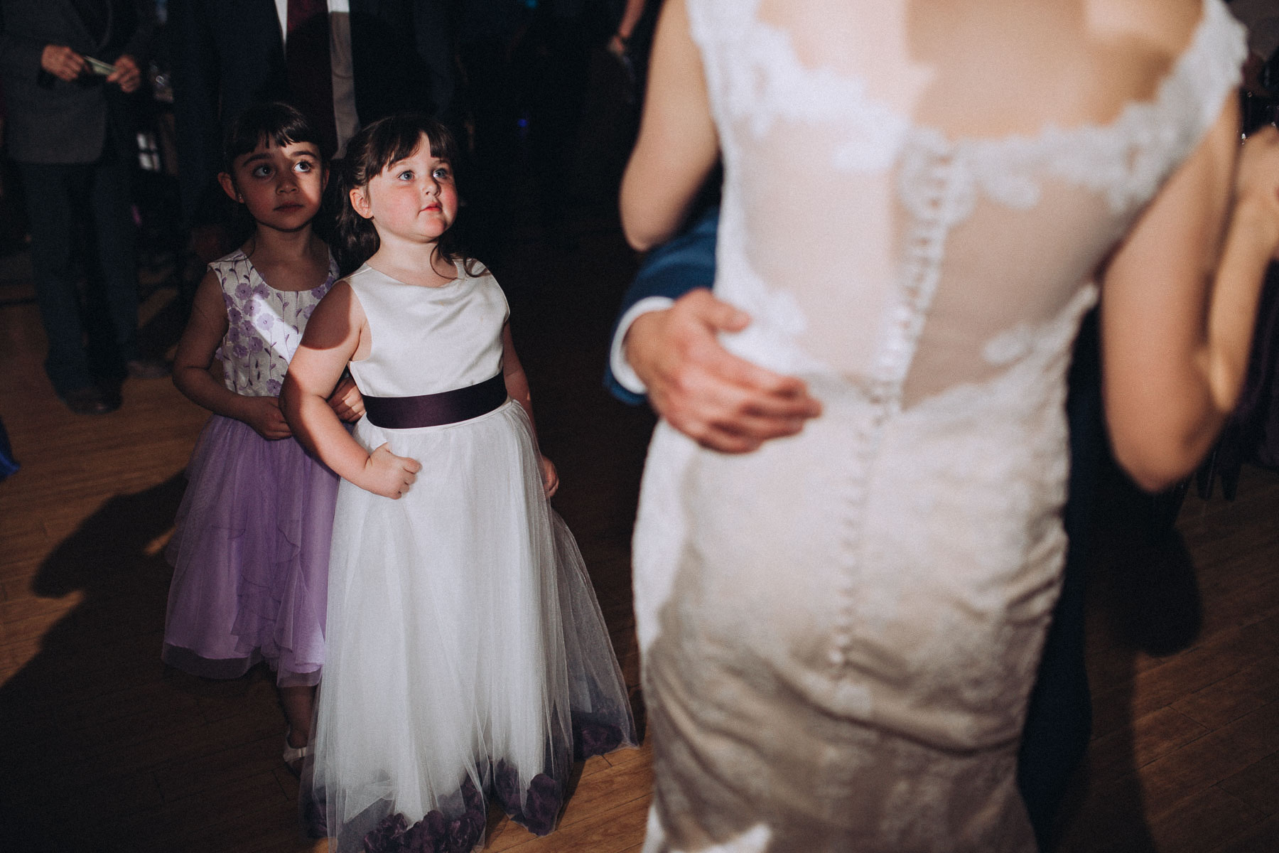 Two girls look on as bride dances during reception at Wedgewood Black Forest