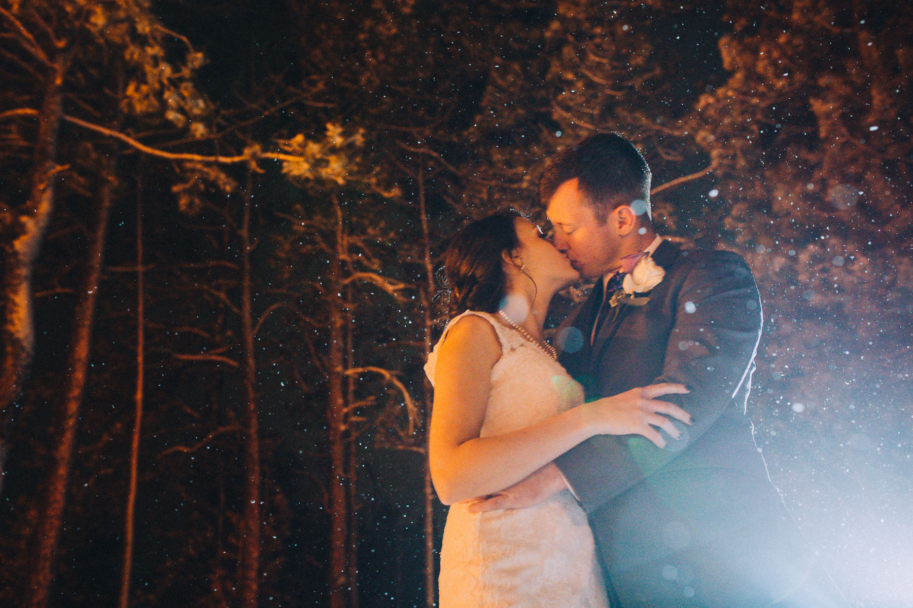 Bride and groom share a kiss at night in front of tall pine trees at Wedgewood Black Forest.