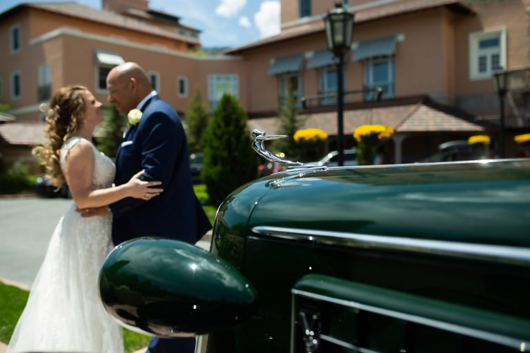 Wedding couple embraces in front of antique car at The Broadmoor.