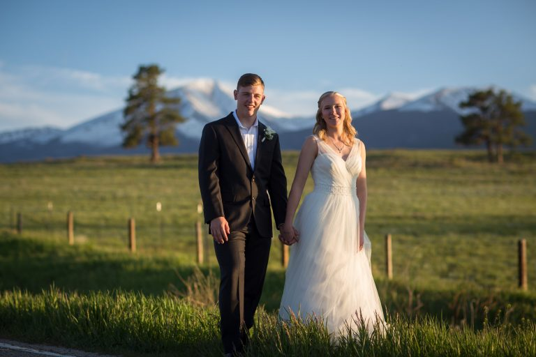 Bride and groom stand in tall grass with the Wet Mountains behind them.