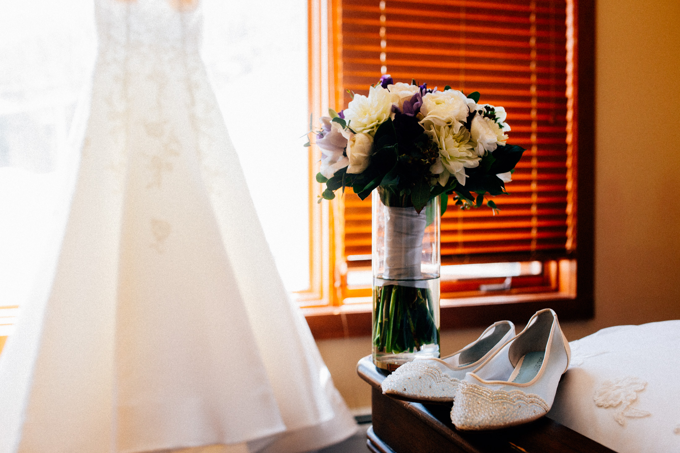 Wedding shoes with flowers and dress.