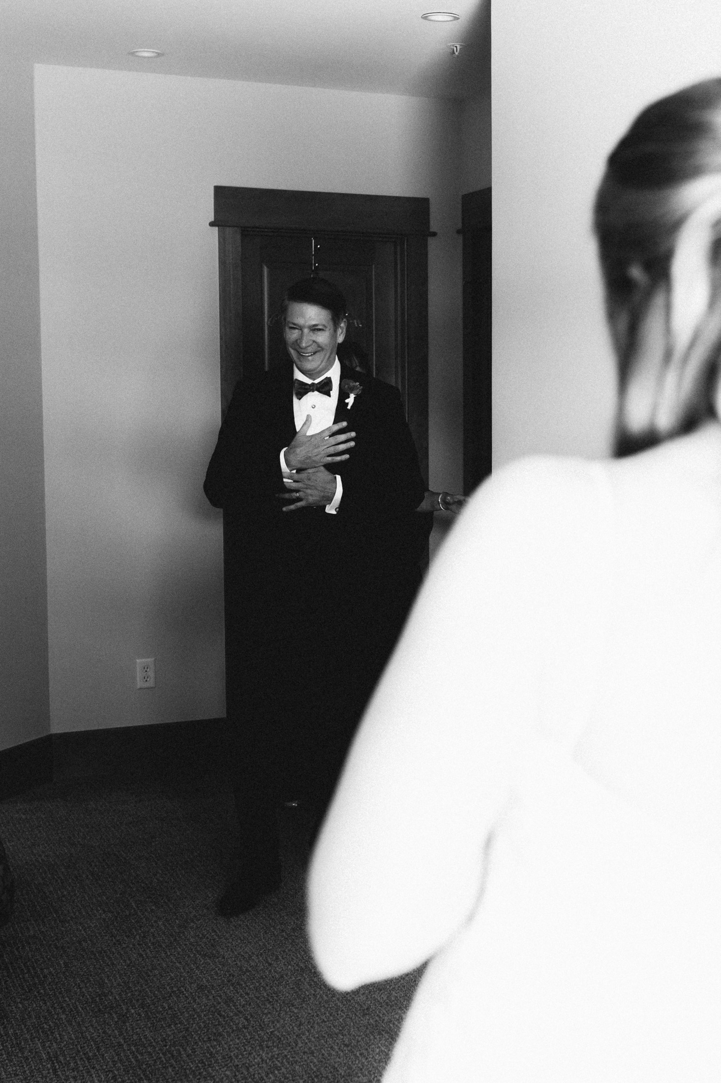 Black and white photo of dad seeing daughter in bridal suite.