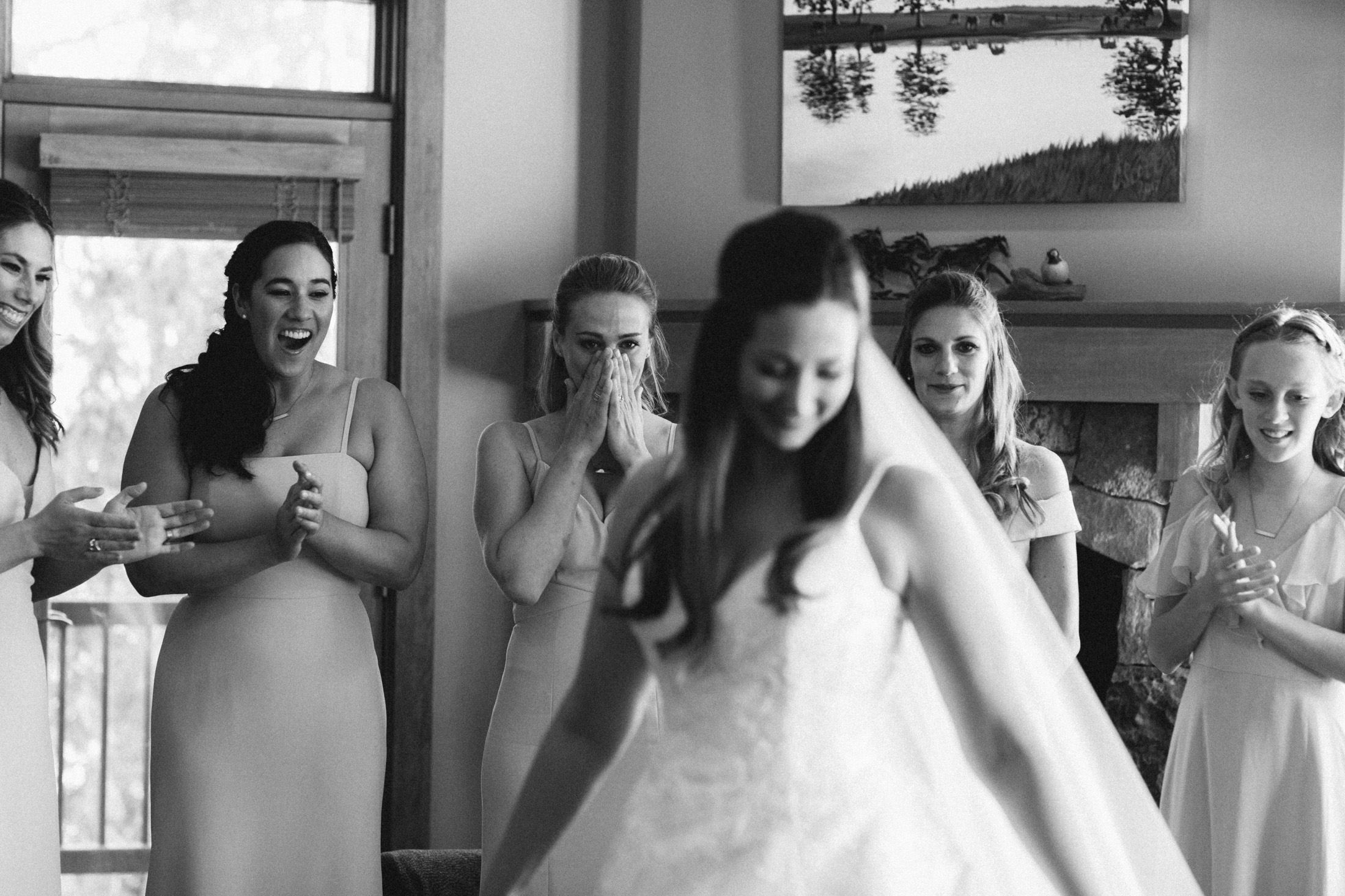 Black and white photo of bridesmaids react to bride in wedding dress.