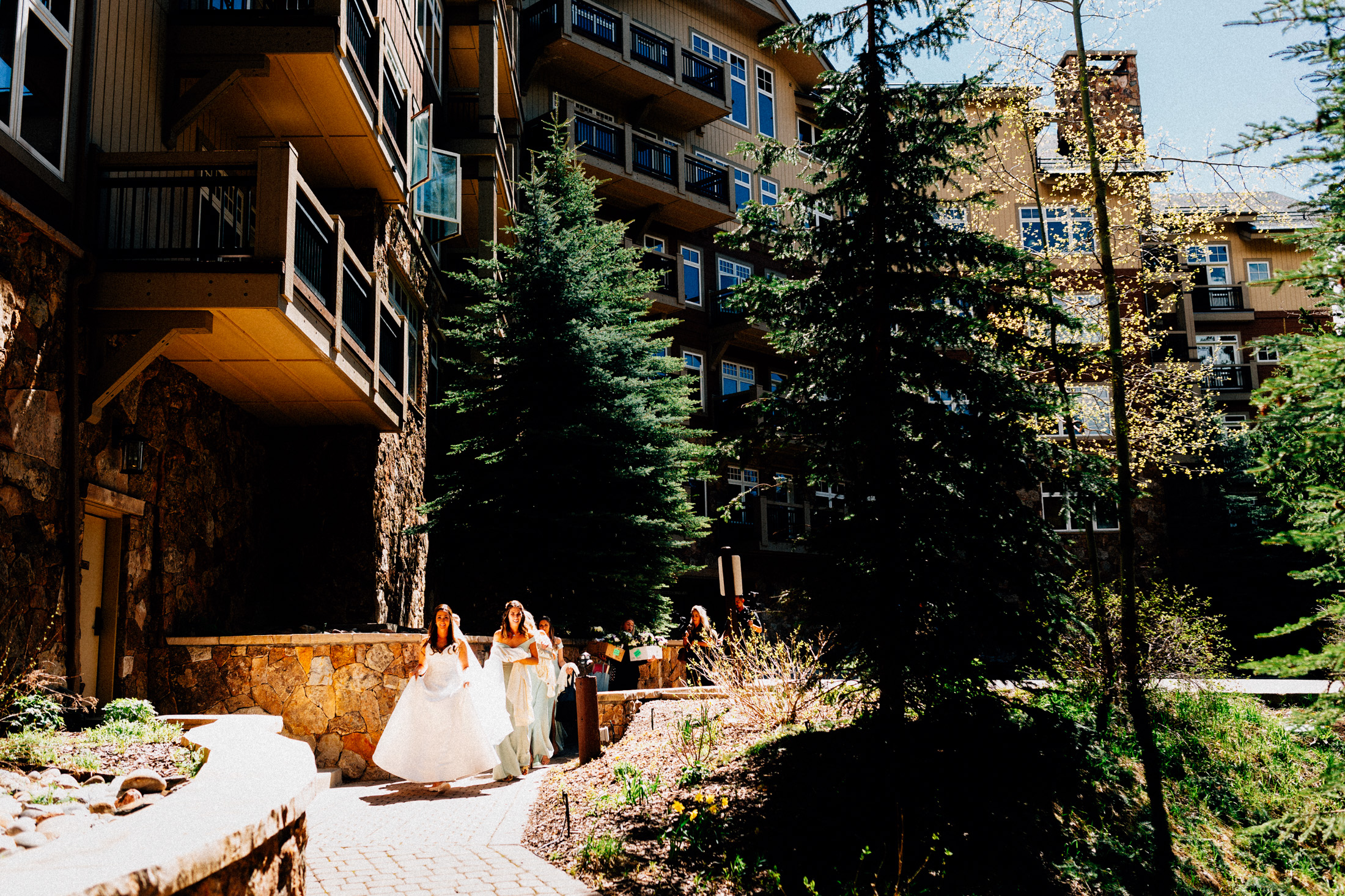 Bride beside Lone Eagle walks in sunlight to the gondola at Center Village.