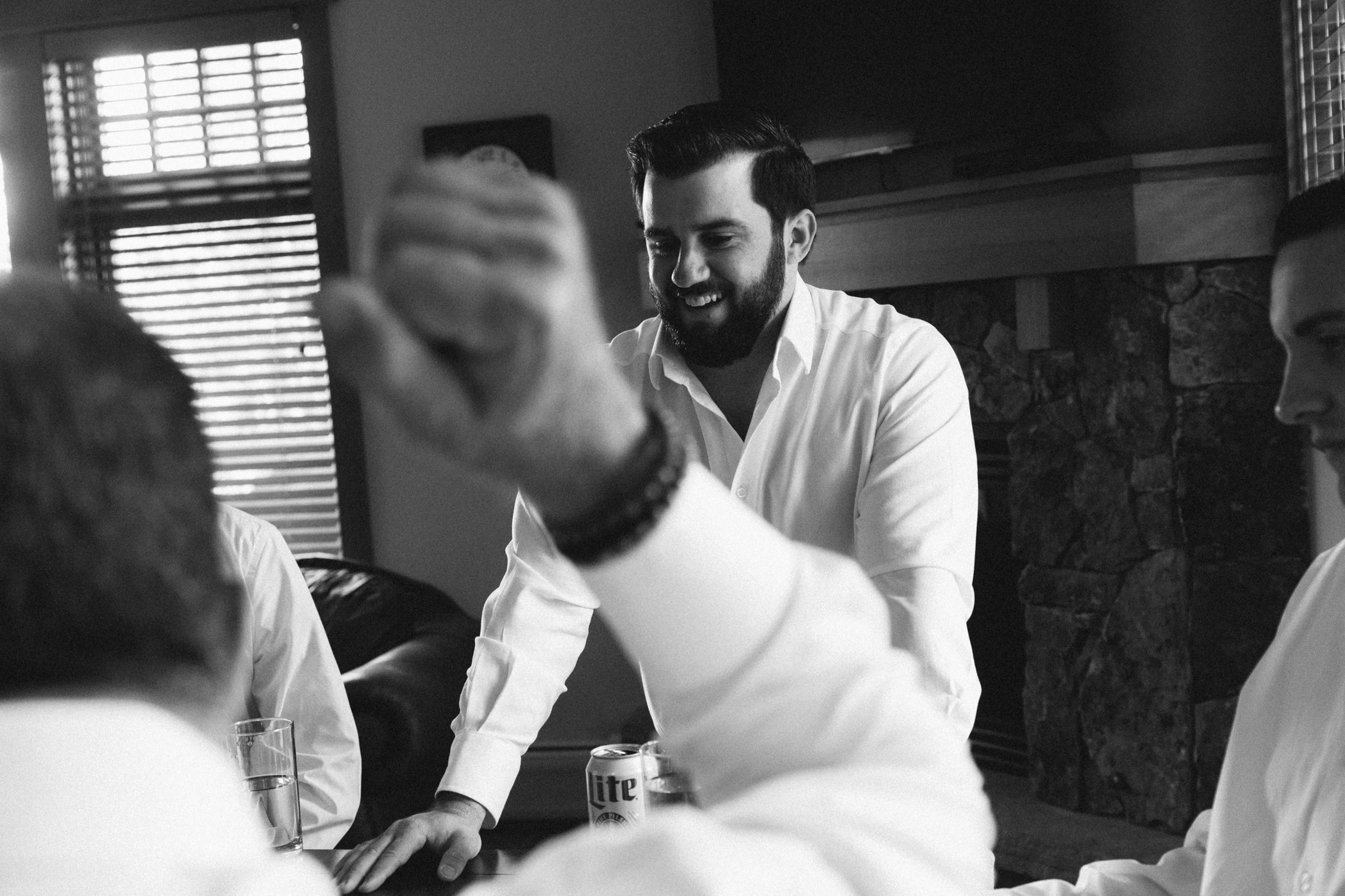 Black and white photo of groom drinking beer with groomsmen in his suite at Lone Eagle.
