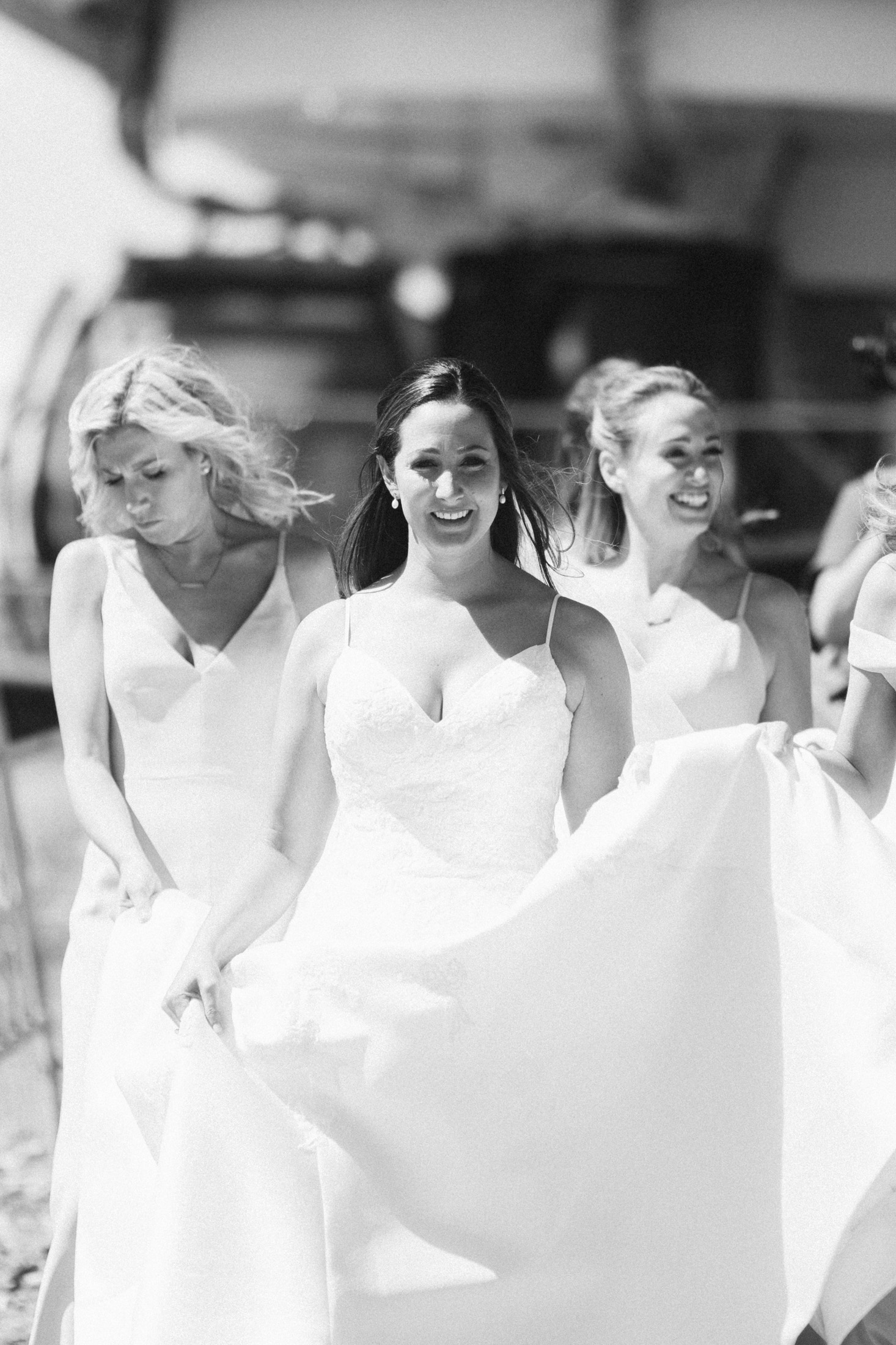 Black and white photo of bride walking with bridesmaids at the top of Keystone Resort.