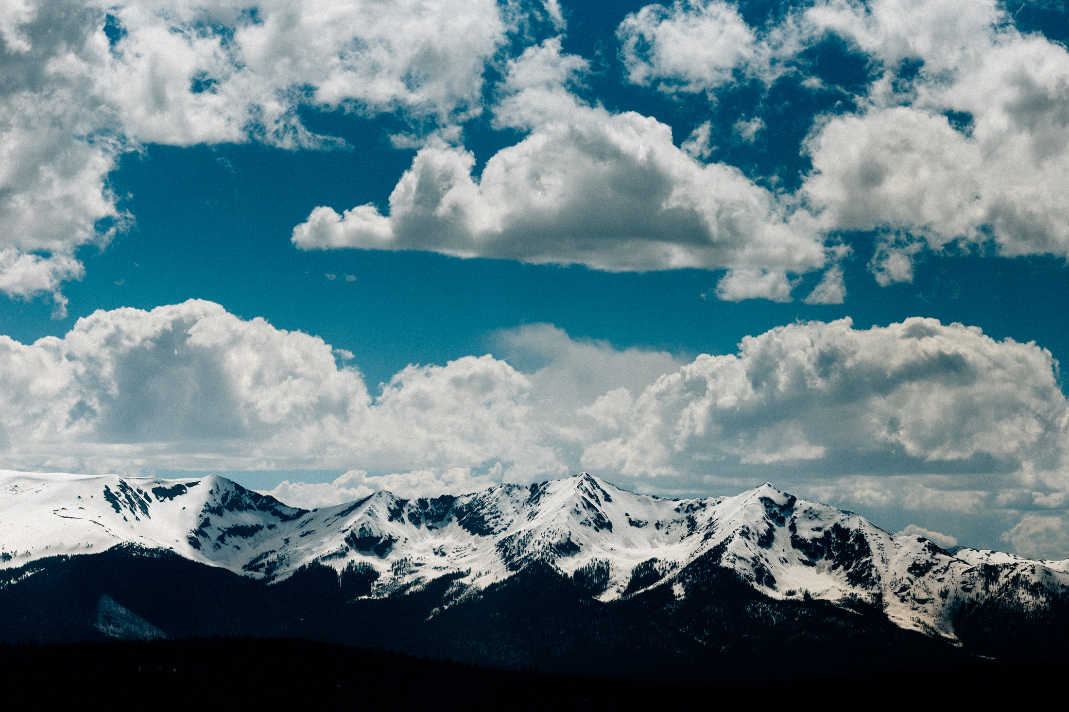 Snow-capped Rocky Mountains with blue sky and clouds at Keystone Resort.