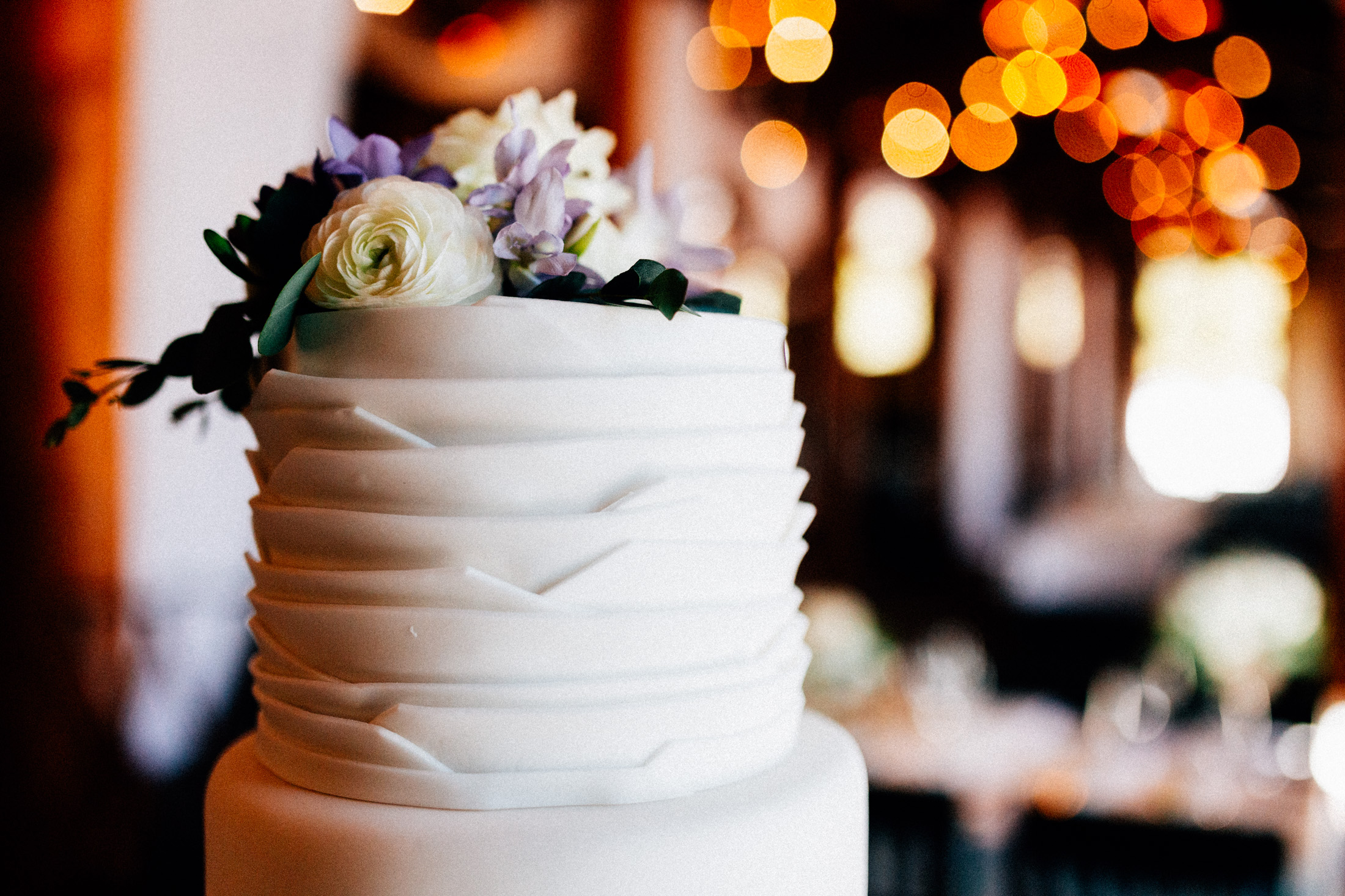 Wedding cake with flowers on top at Timber Ridge Lodge.