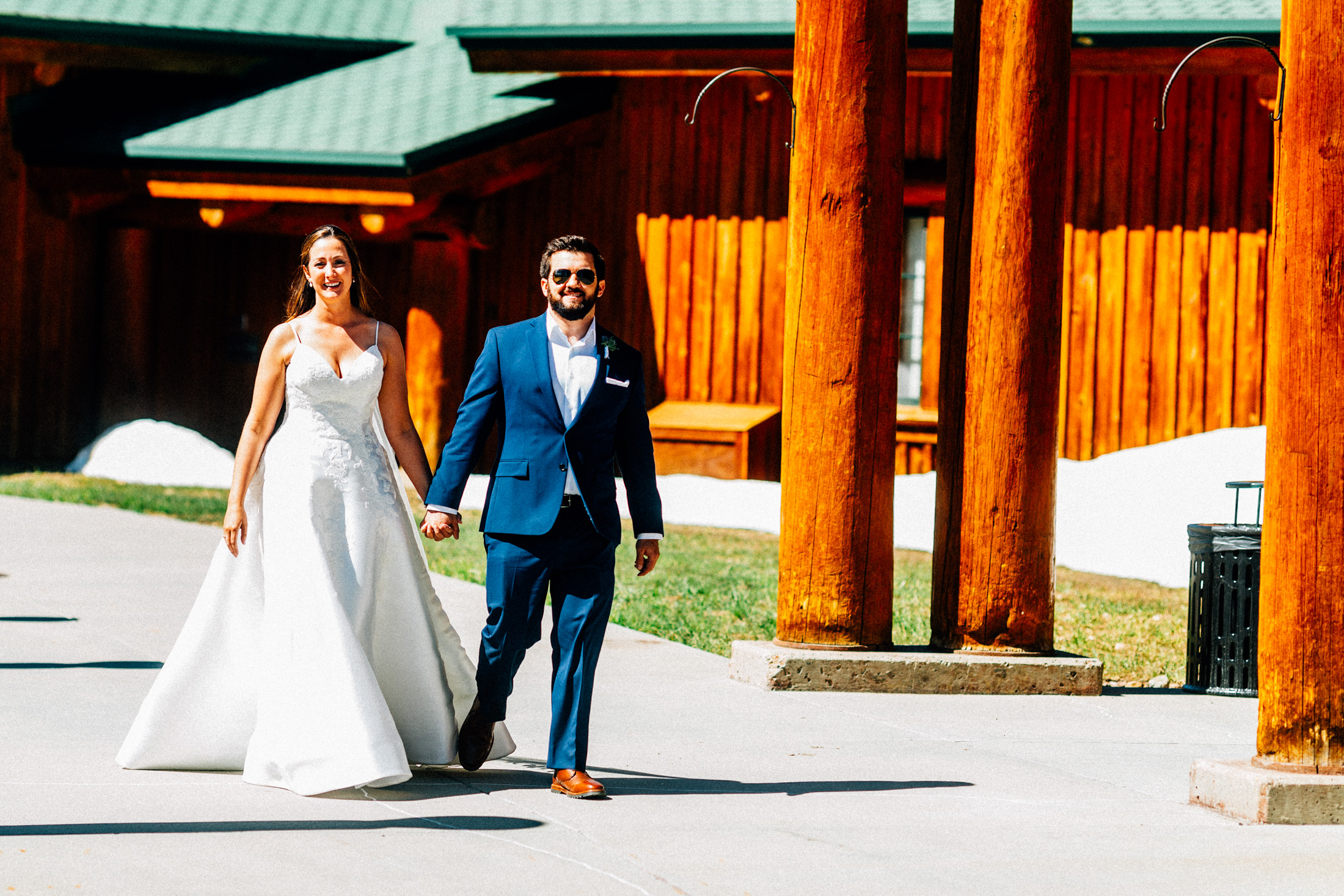 Bride and groom walk together holding hands outside of Timber Ridge Lodge.