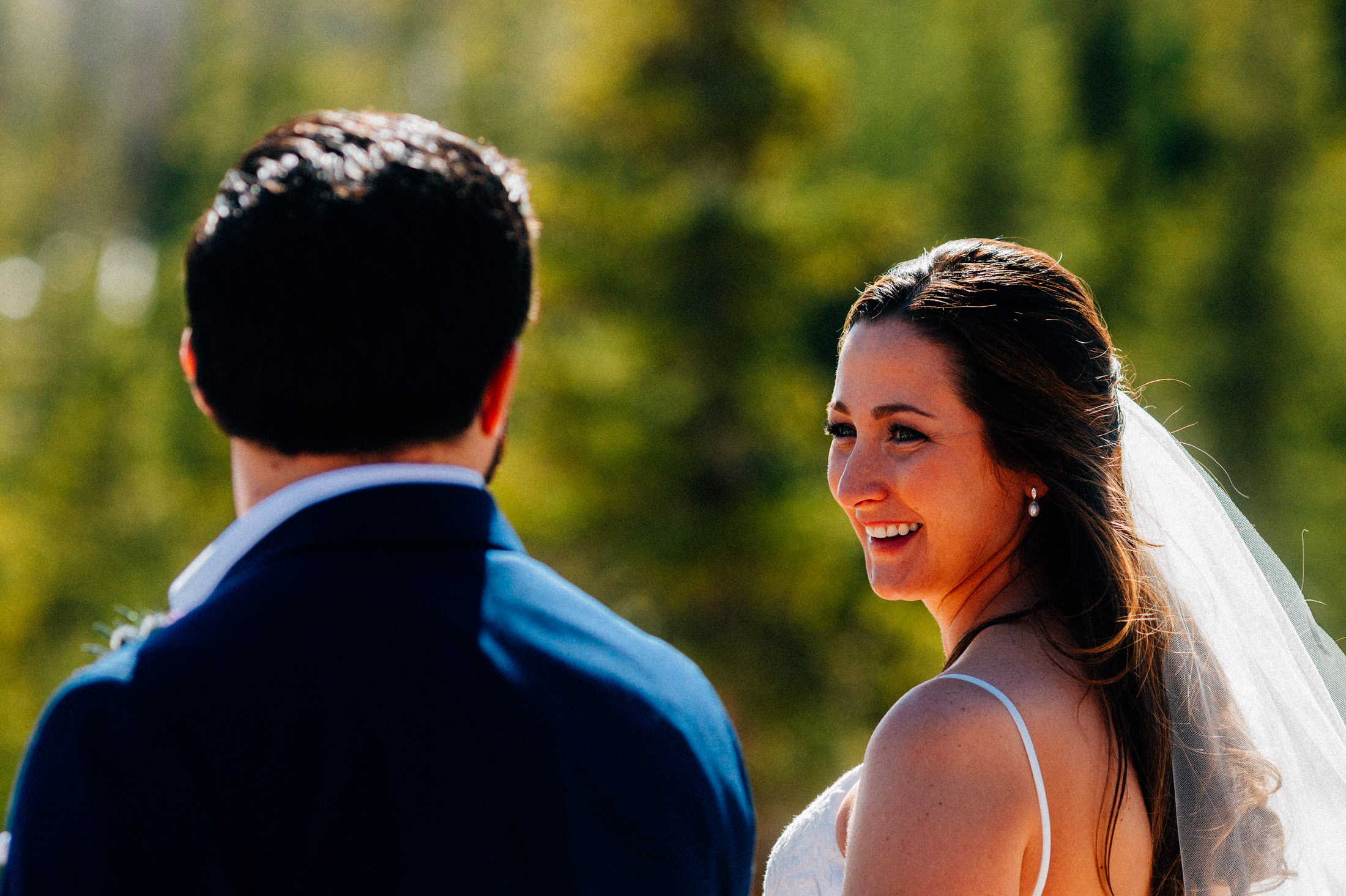 Bride looks at groom on the deck at Timber Ridge Lodge.