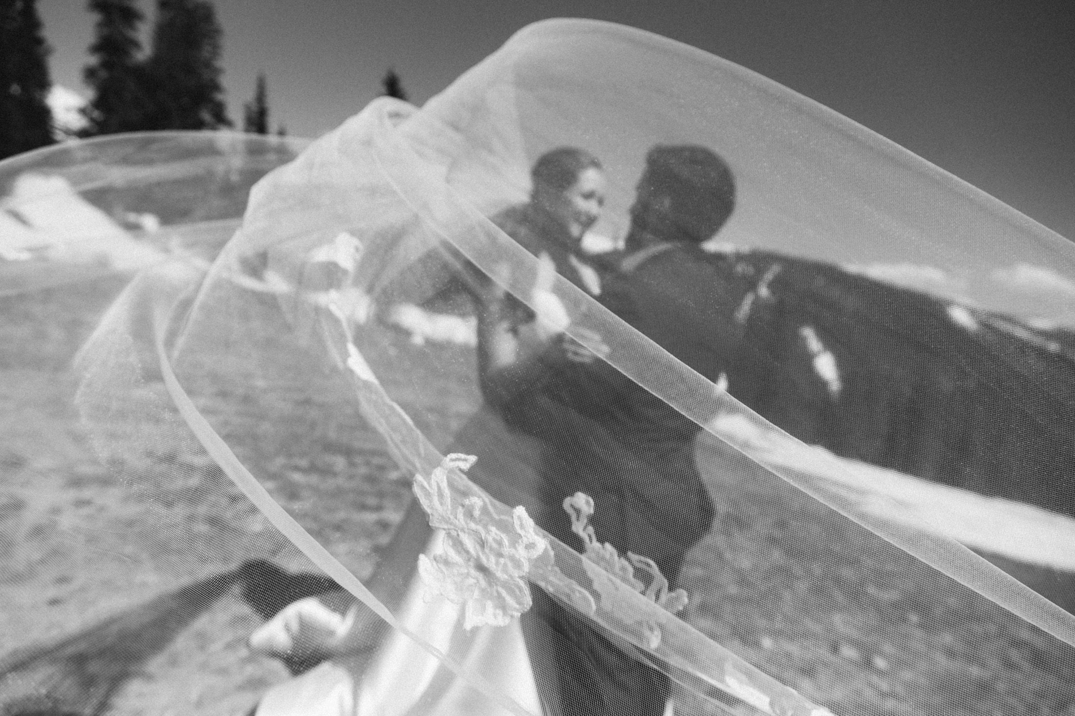 Black and white photo of bride and groom embracing with veil blowing in the wind.