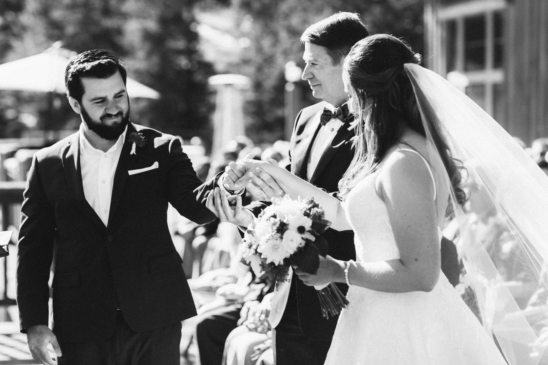 Black and white photo of father handing his daughter's hand to groom.