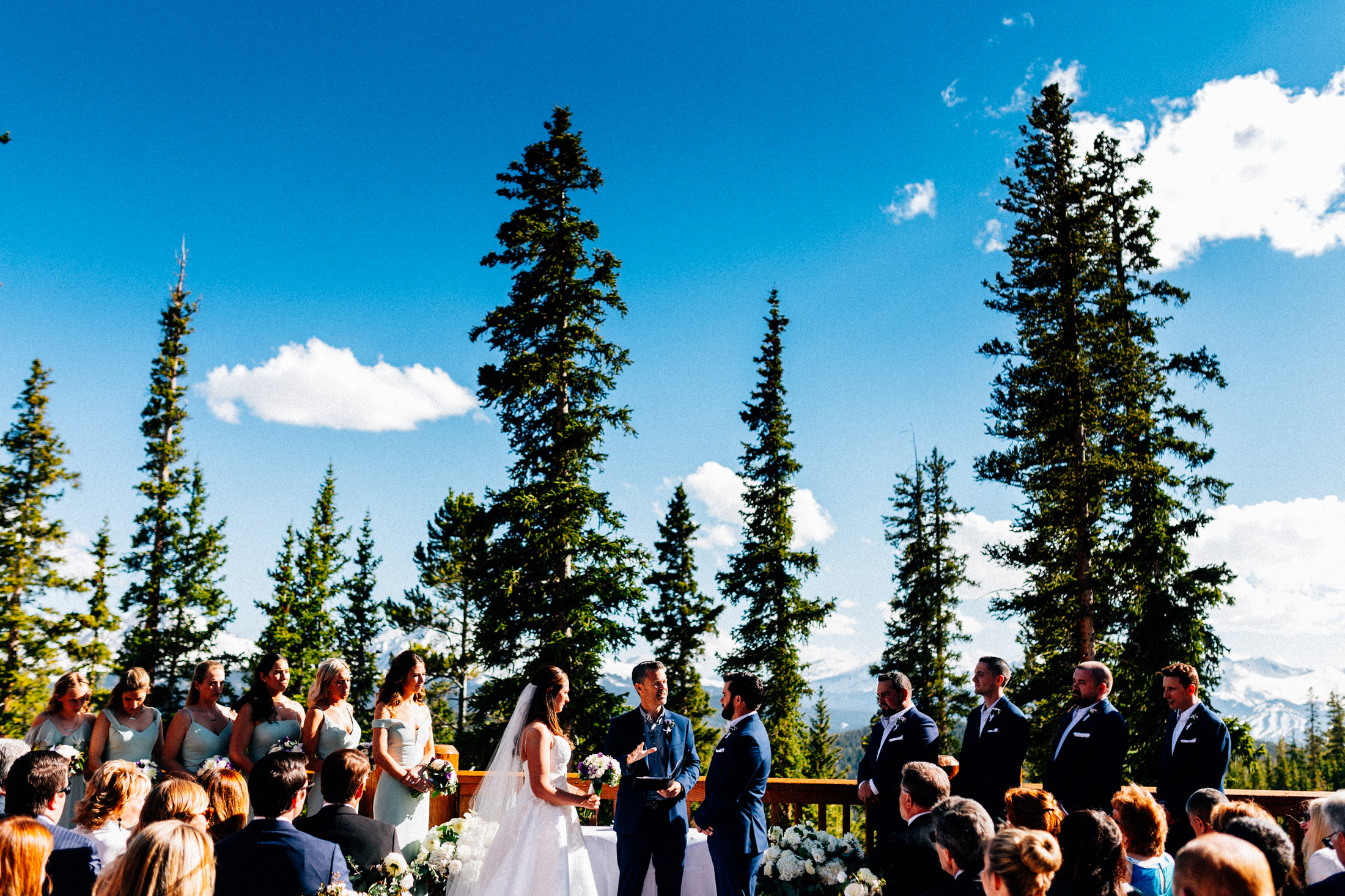 Bride and groom with wedding party stand at altar on the deck of Timber Ridge Lodge with pine trees and blue sky.