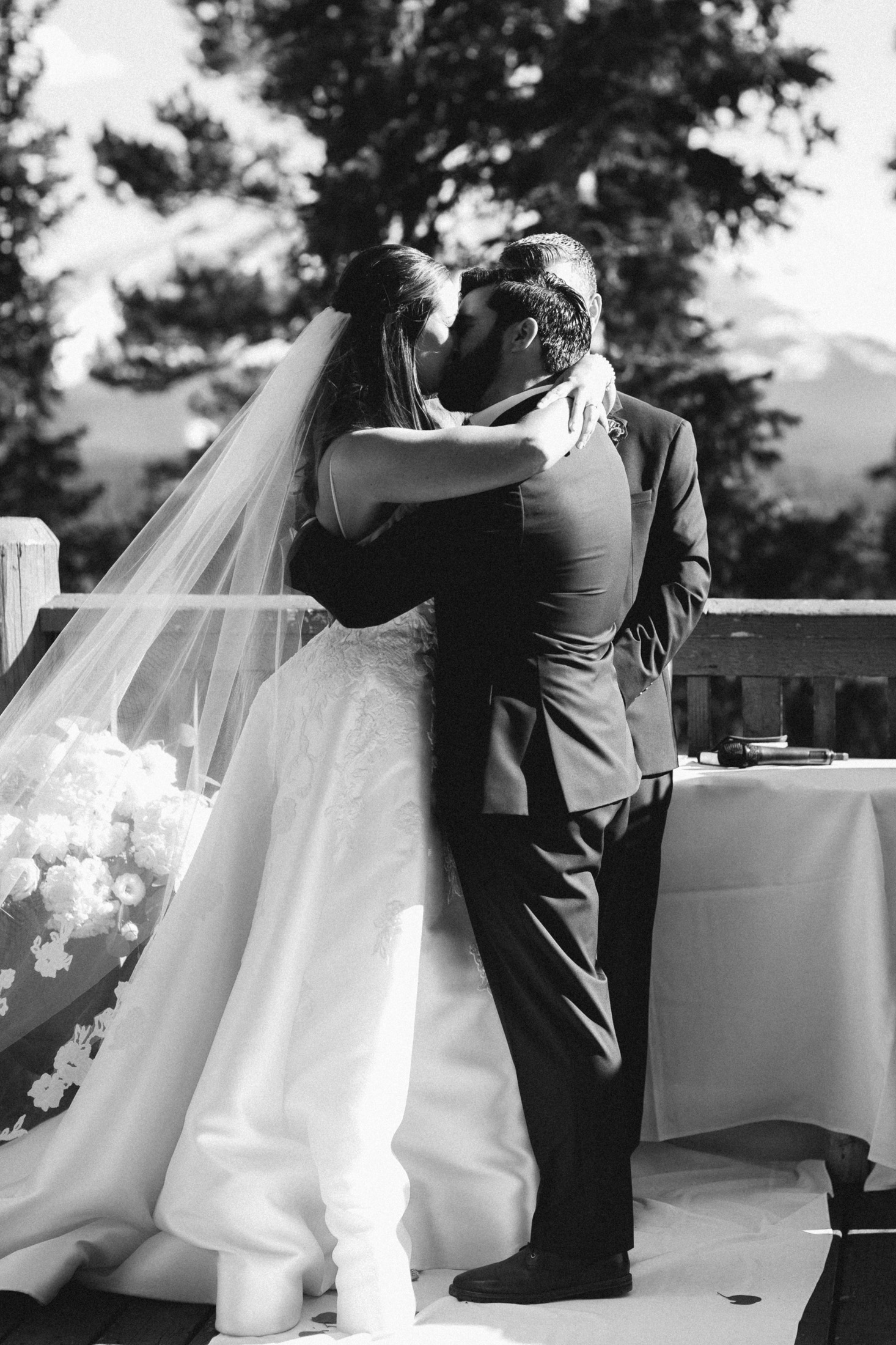 Black and white photo of bride and groom kissing at the end of the wedding ceremony.