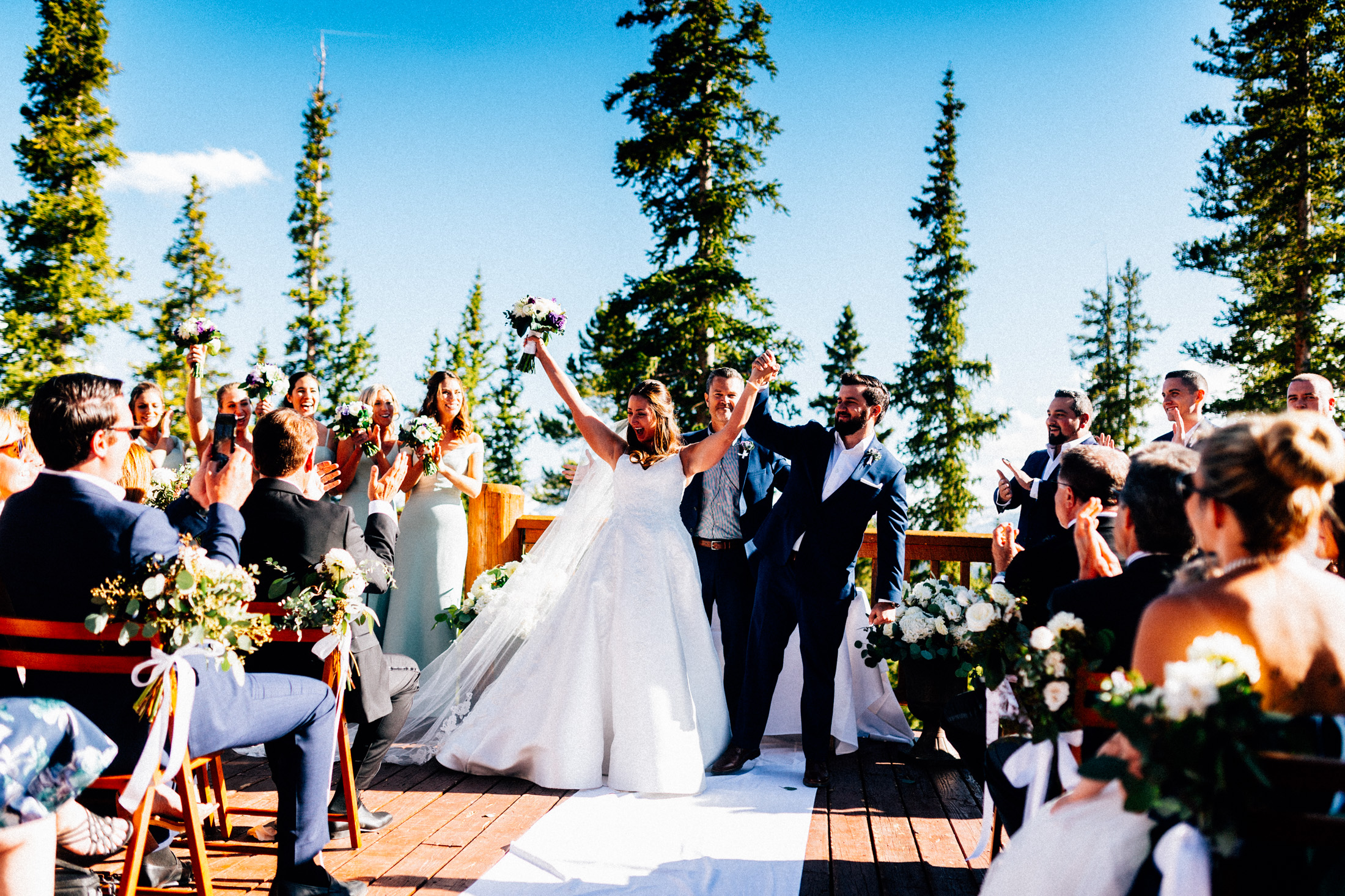Bride and groom at the altar raise their hands in celebration.