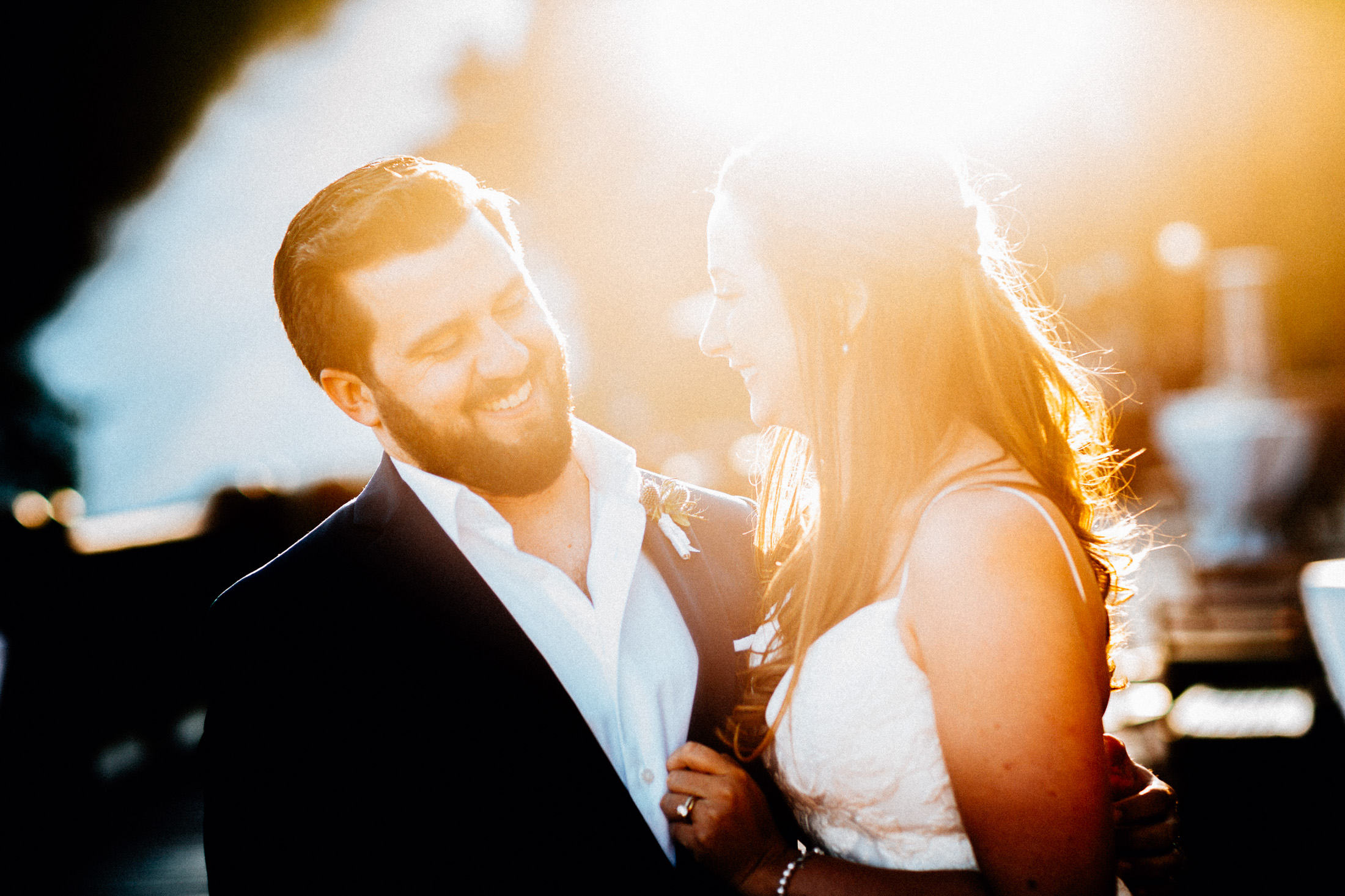 Bride and groom laugh together in sunlight.