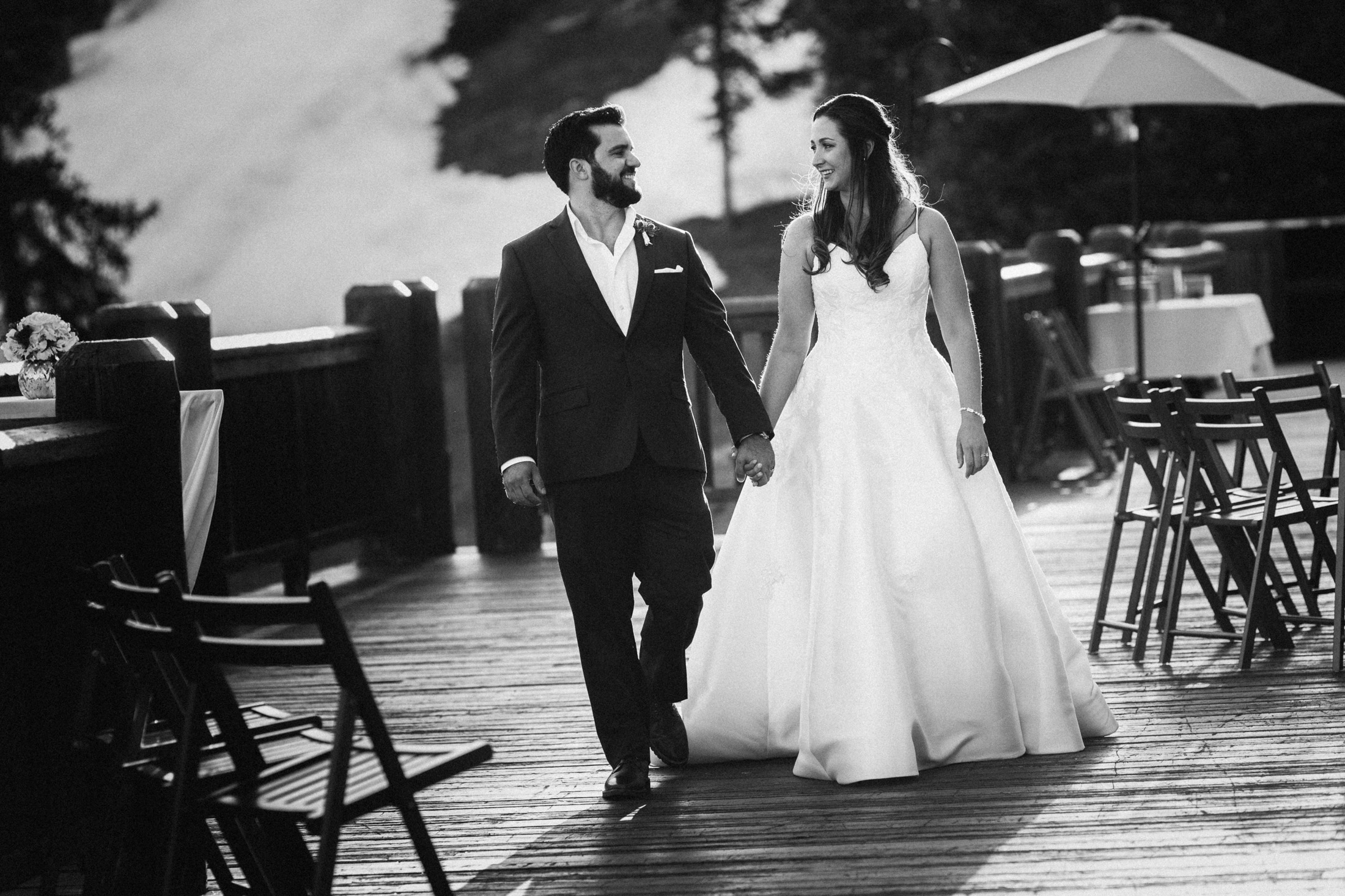 Black and white photo of bride and groom walking hand-in-hand on the deck of the Timber Ridge Lodge.
