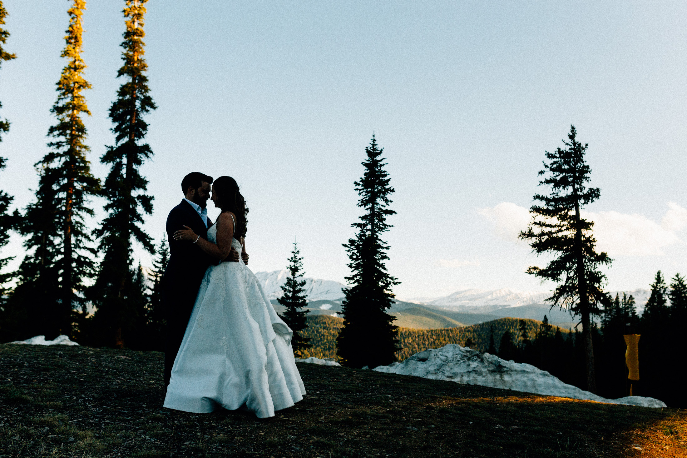 Bride and groom embrace at sunset in front of pine trees and snow capped mountains at Timber Ridge Lodge.