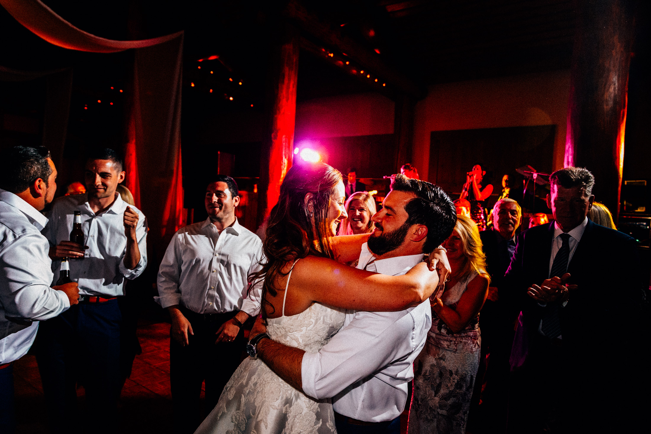Bride embraces groom on dance floor during wedding reception inside Timber Ridge Lodge.