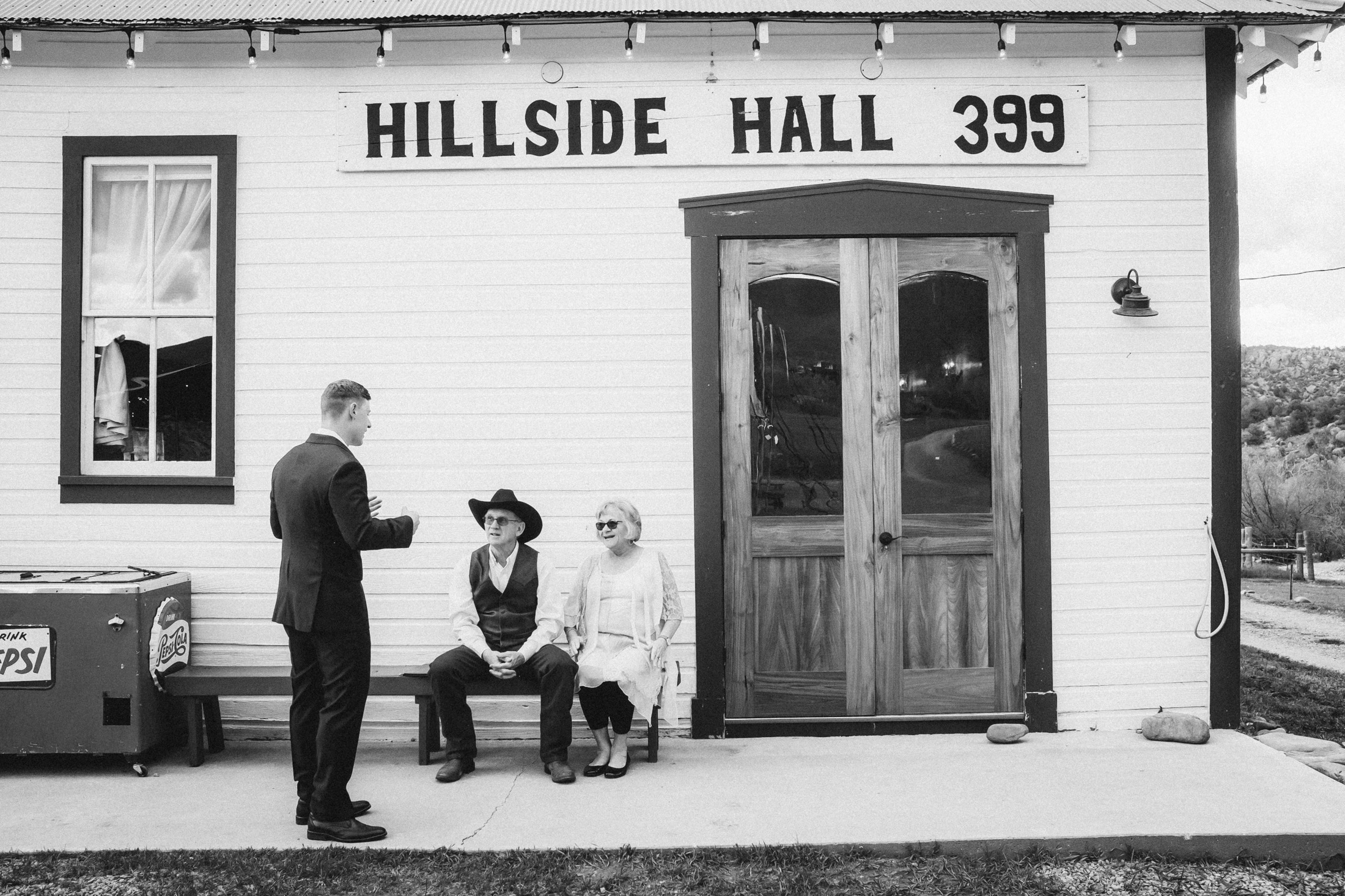 Black and white picture of groom talking with guests at Willow Vale Events.