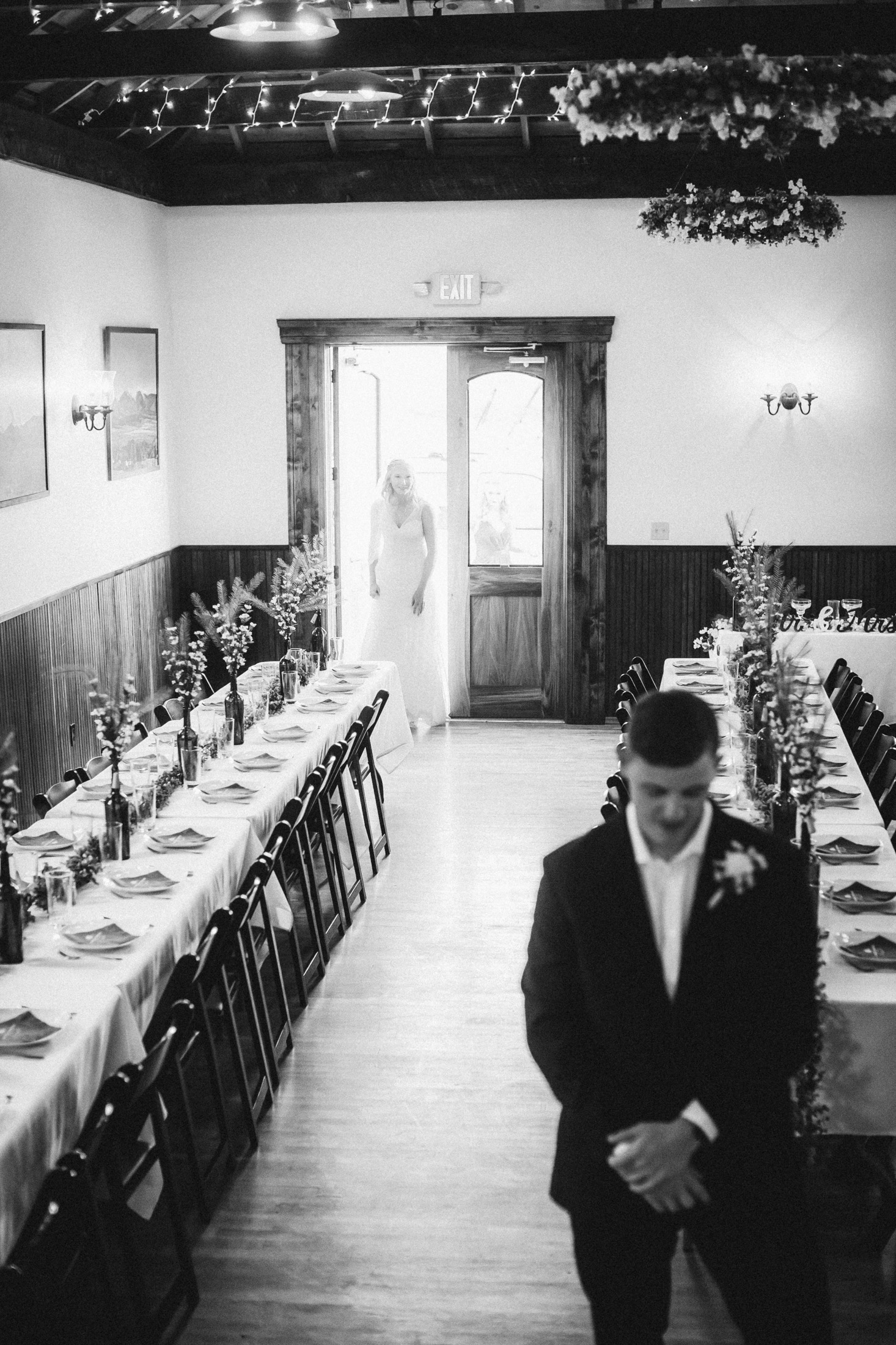 Black and white picture of bride seeing groom inside banquest hall at Willow Vale Events.