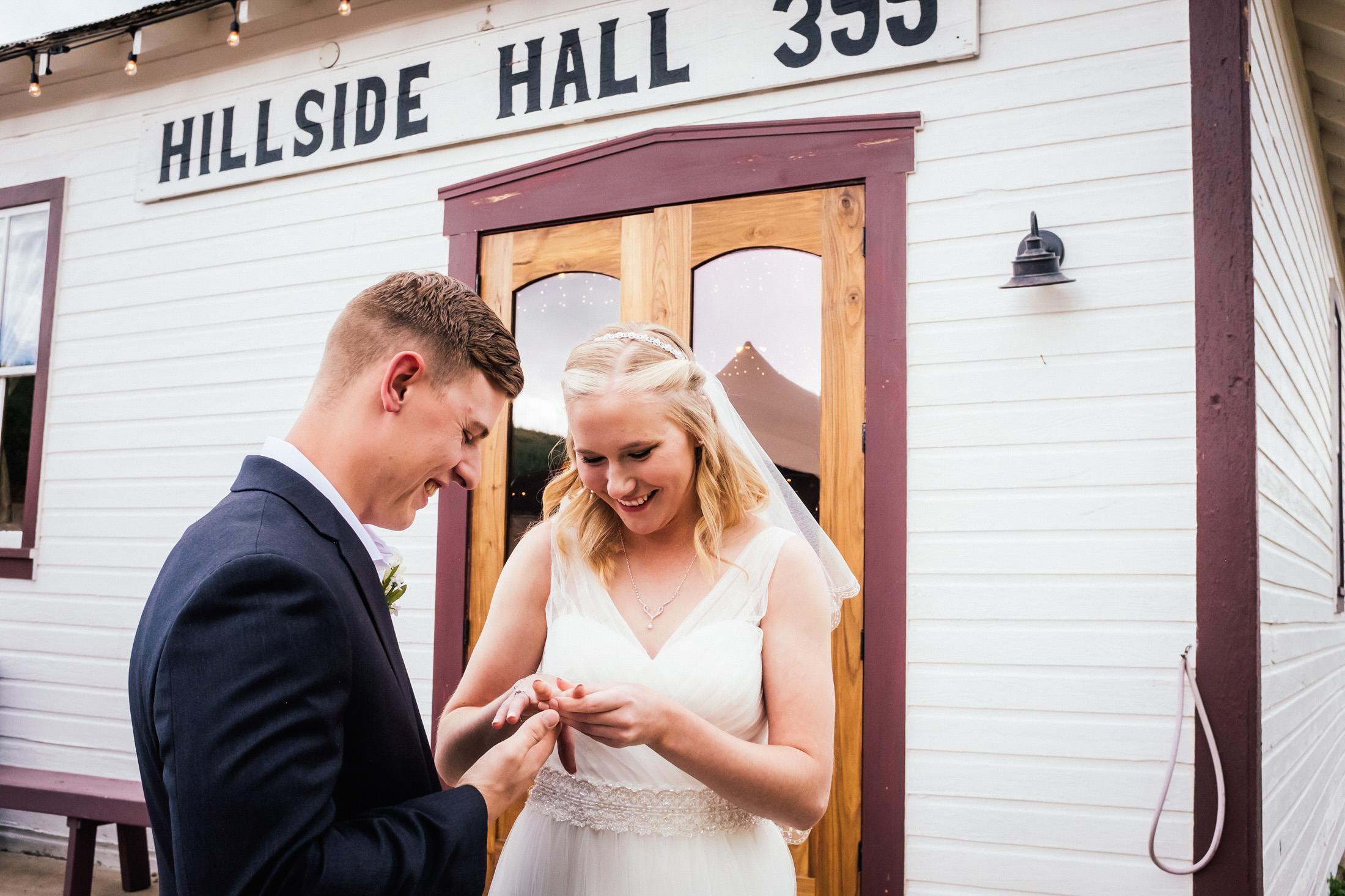 Bride and groom looking at wedding rings outside banquet hall at Willow Vale Events.