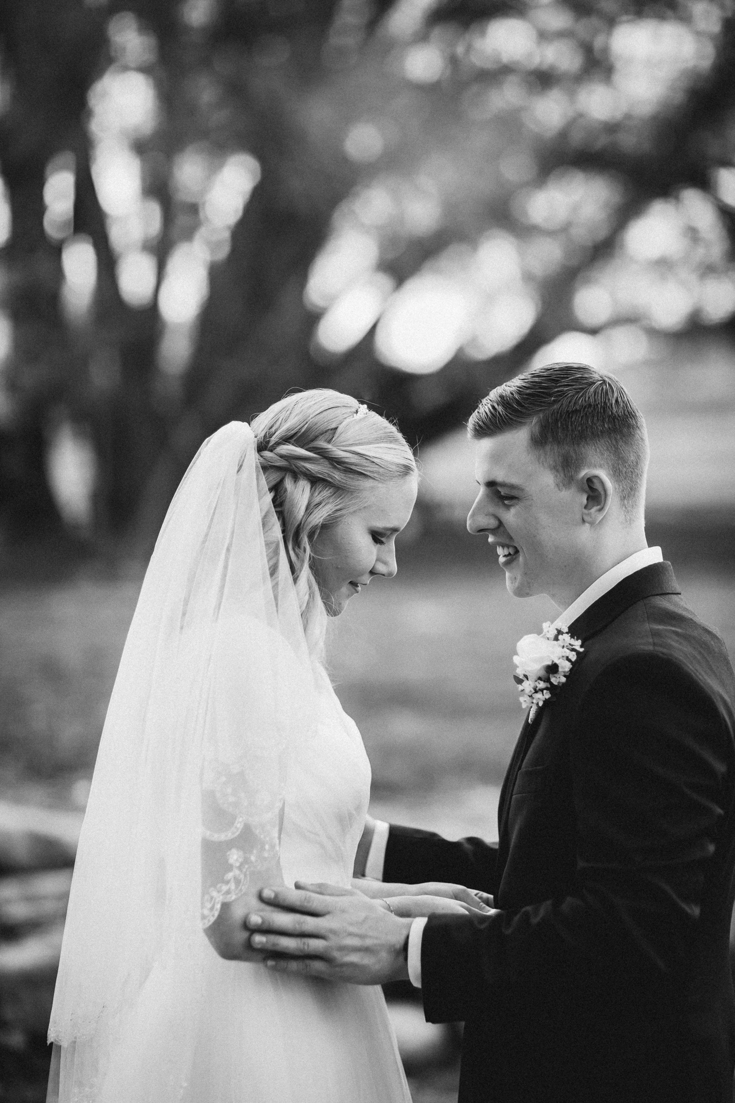 Black and white photograph of bride and groom embracing underneath Willow trees at Willow Vale Events.