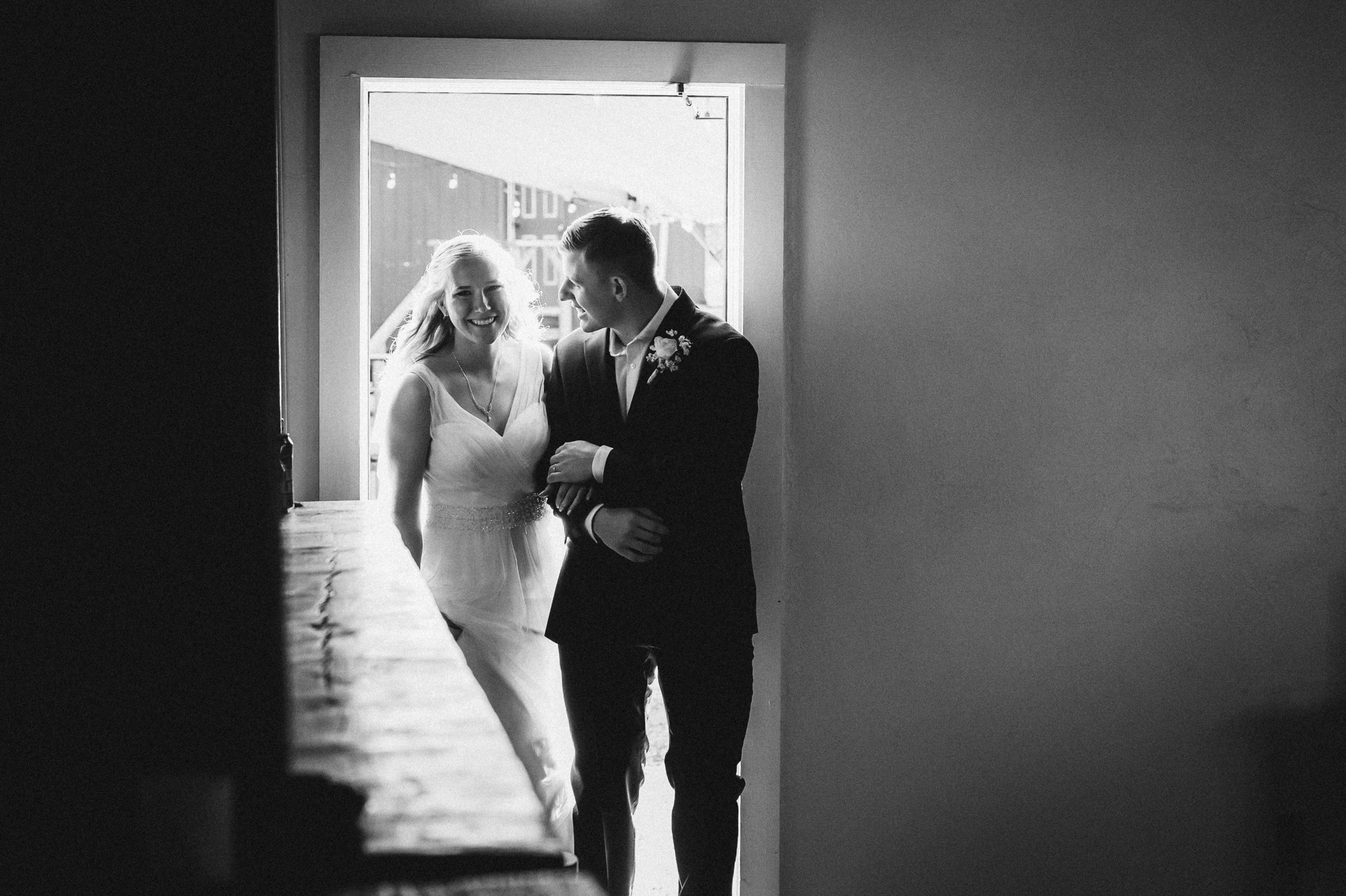 Black and white photograph of bride and groom entering banquet hall at Willow Vale Events.