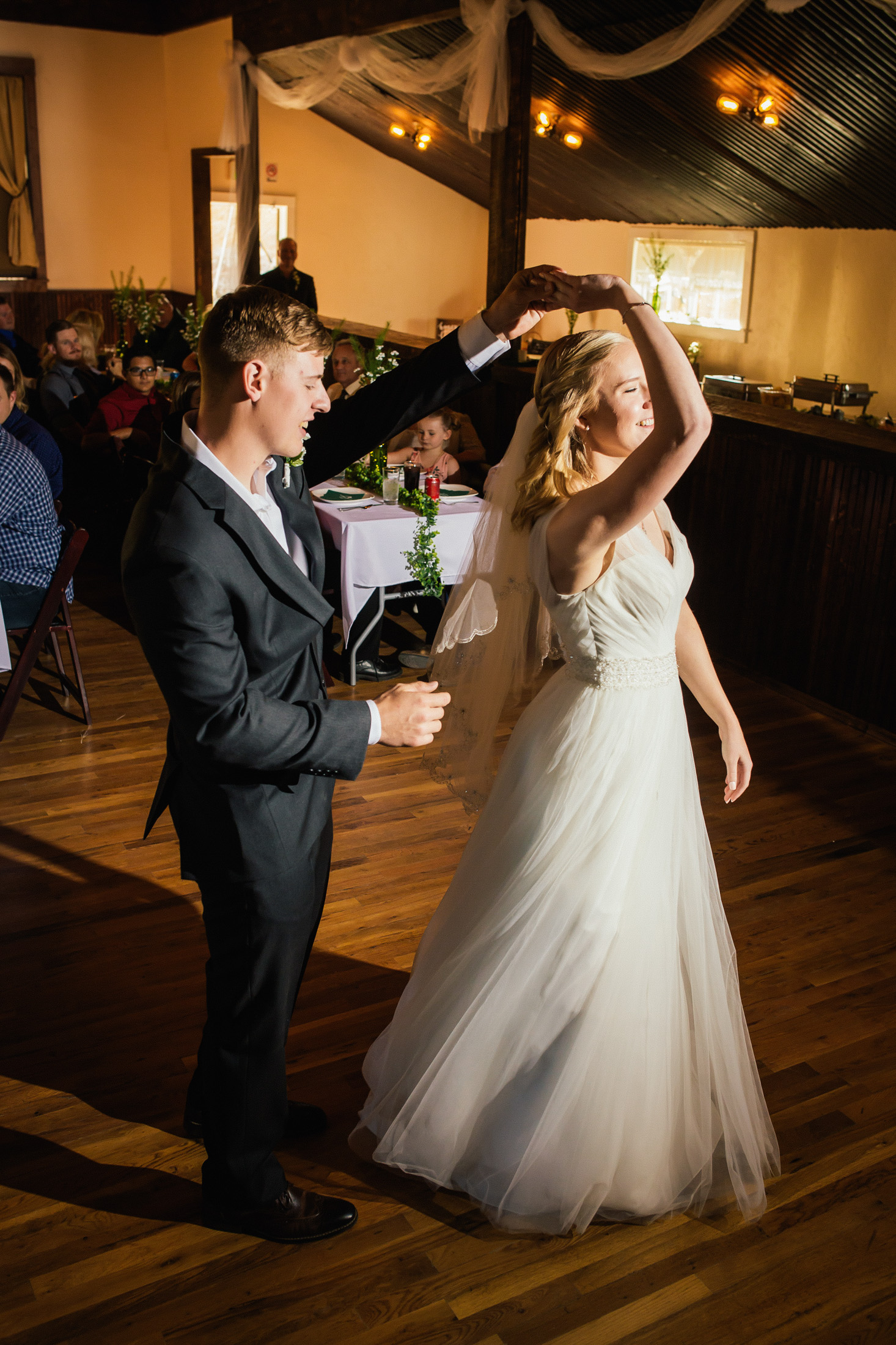 Groom twirls bride during first dance inside banquet hall at Willow Vale Events.