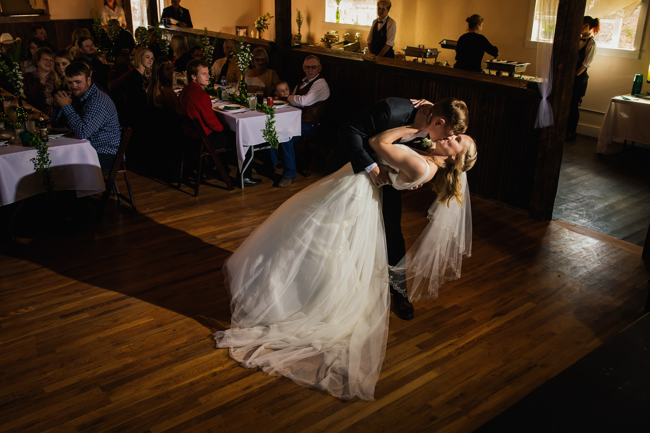 Groom dips bride and kisses her during first dance at Willow Vale Events.