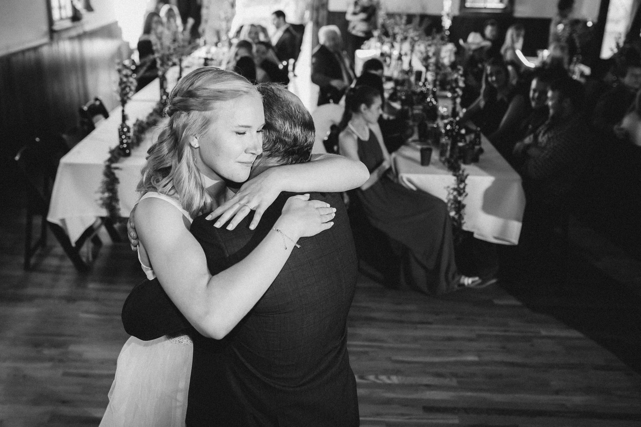 Bride hugs father during dance inside banquet hall at Willow Vale Events.