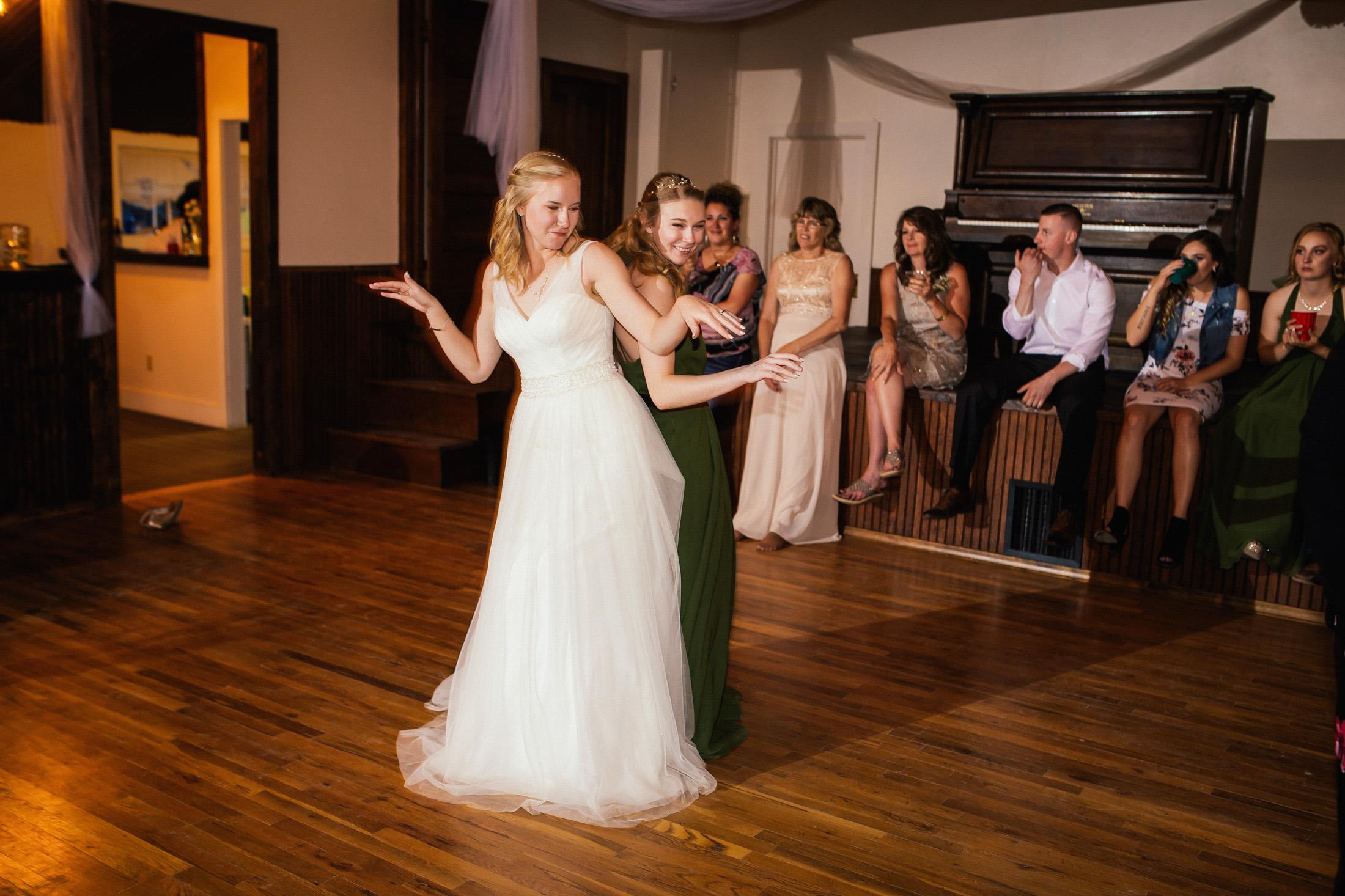 Bride dances with friends inside banquet hall.