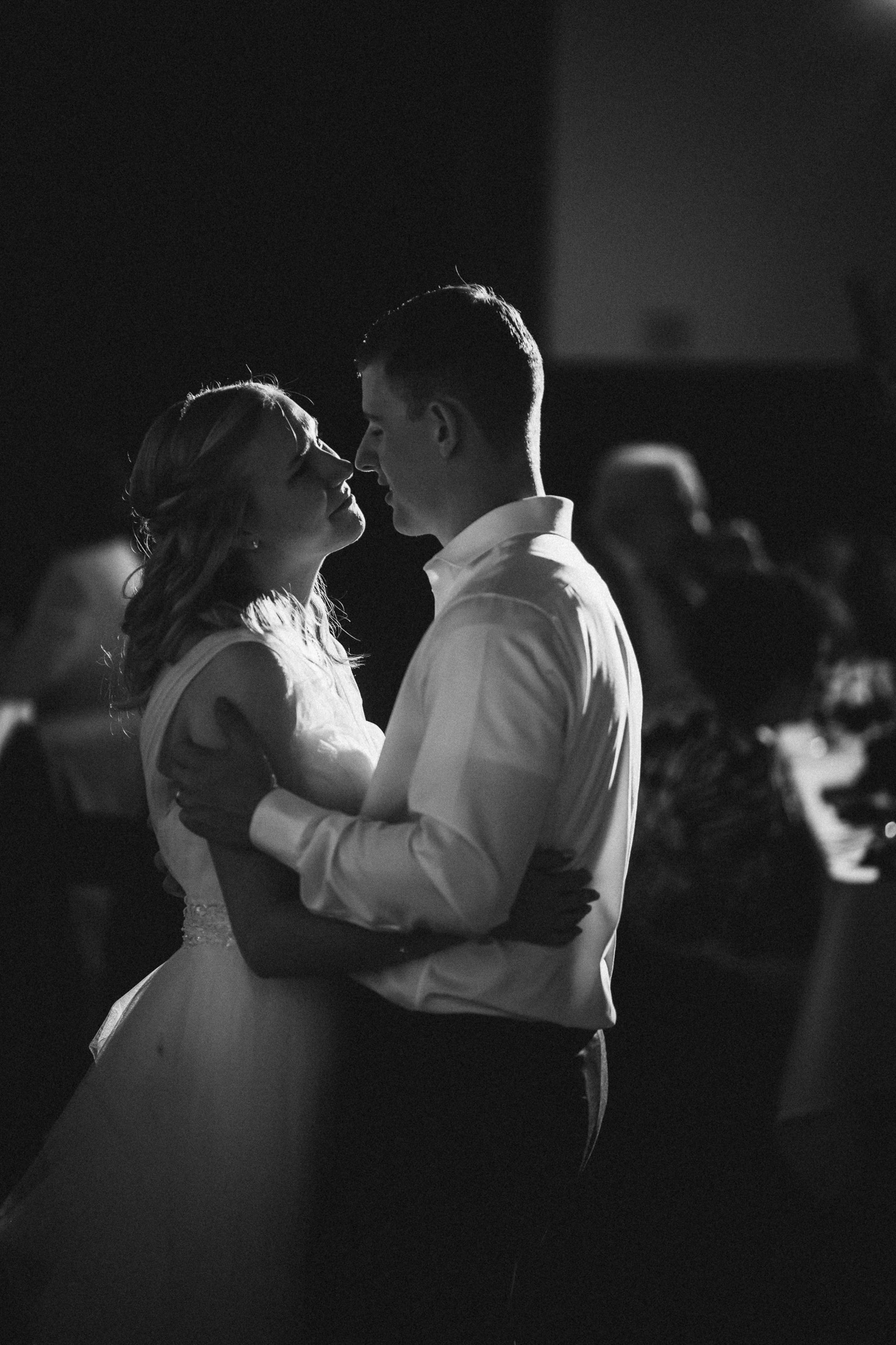 Black and white picture of bride and groom dancing.