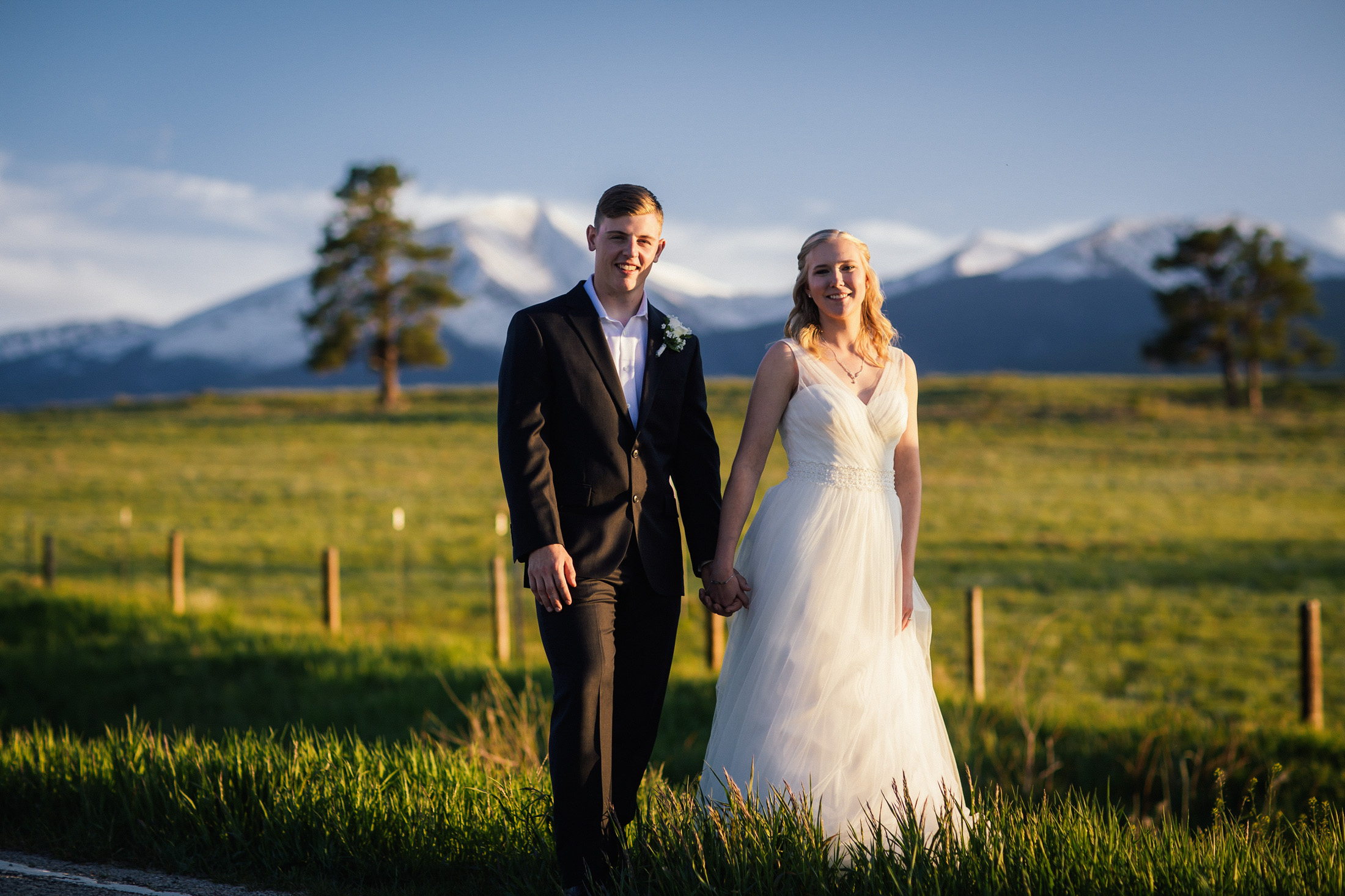 Bride and groom hold hands in field with mountains in the background.