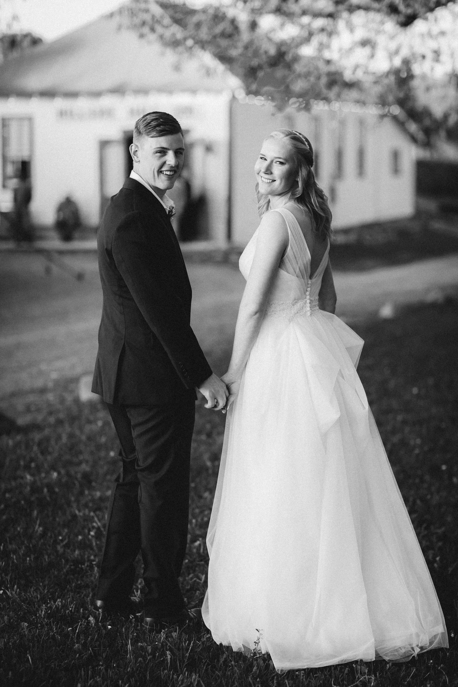 Black and white picture of bride and groom holding hands in front of banquet hall at Willow Vale Events.