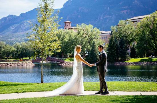 Wedding couple holds hands in front of The Broadmoor's west tower and Cheyenne Mountain.