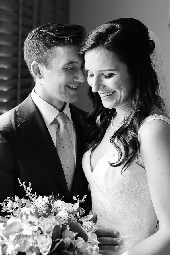 Wedding couple holds each other and laughs together.