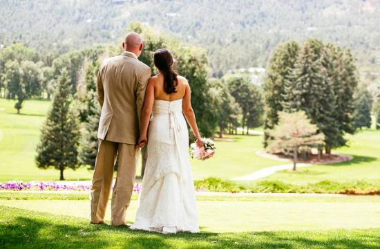 Couple holds hands on their wedding day and looks at Cheyenne Mountain.
