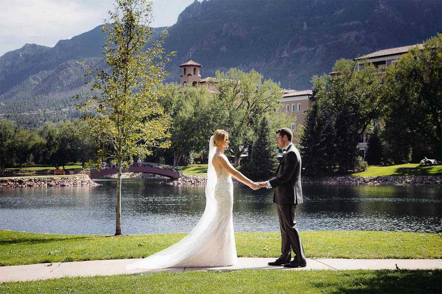 Couple holds hands in front of The Broadmoor's West Tower.