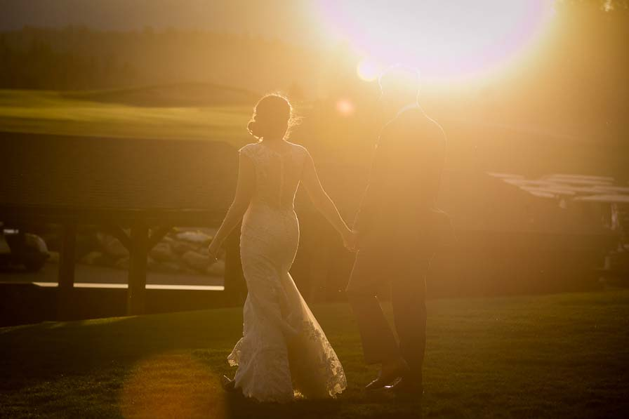 Wedding couple holds hands and walks together during sunset.