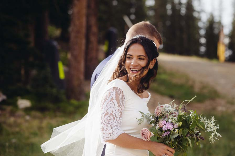 Bride holds bouquet and looks back after wedding ceremony.