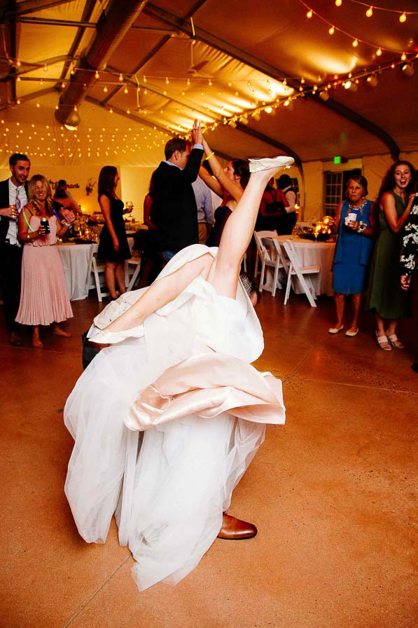 Bride in wedding dress dances with leg up in the air.