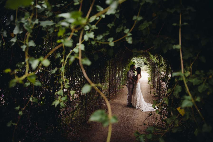 Couple embraces in a garden tunnel.