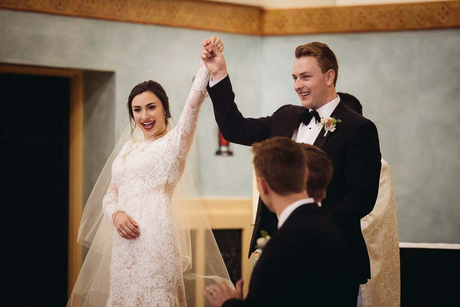 Bride and groom raise hands together in celebration after wedding ceremony.
