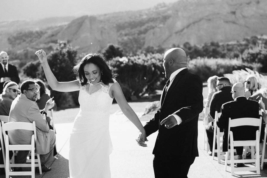 Bride celebrates as she walks down the aisle with groom after ceremony.